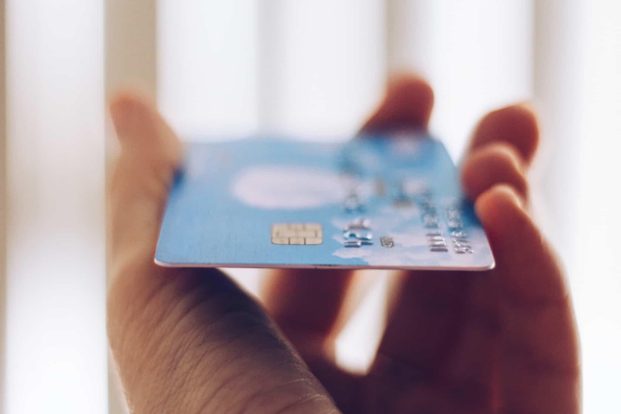 pessoa a segura num cartão de pagamentos