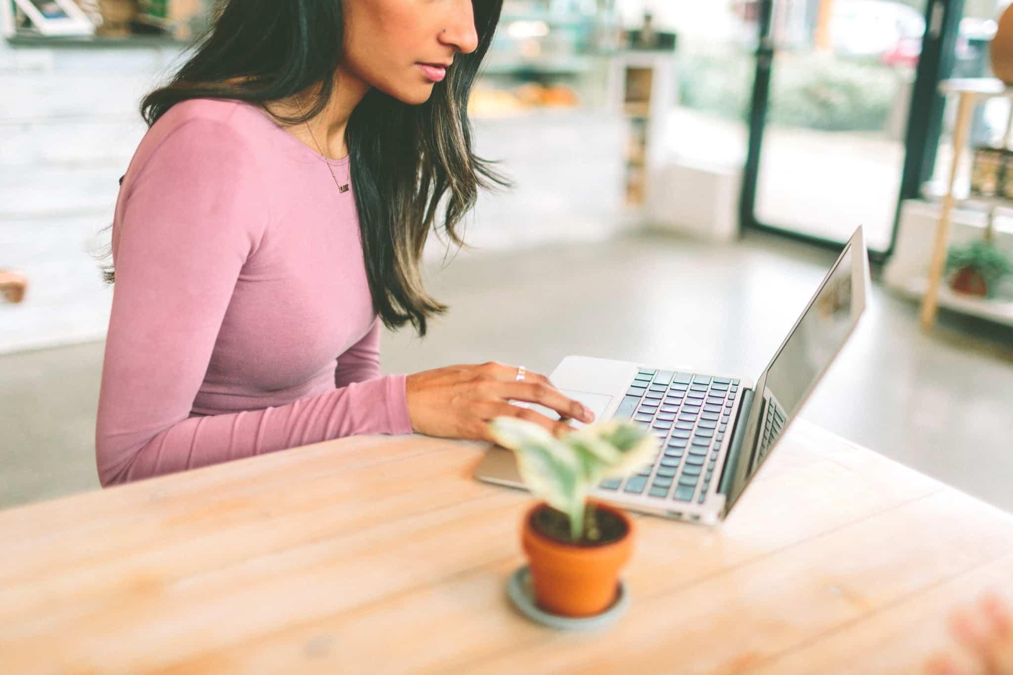 rapariga de camisola cor de rosa a trabalhar no seu computador portátil
