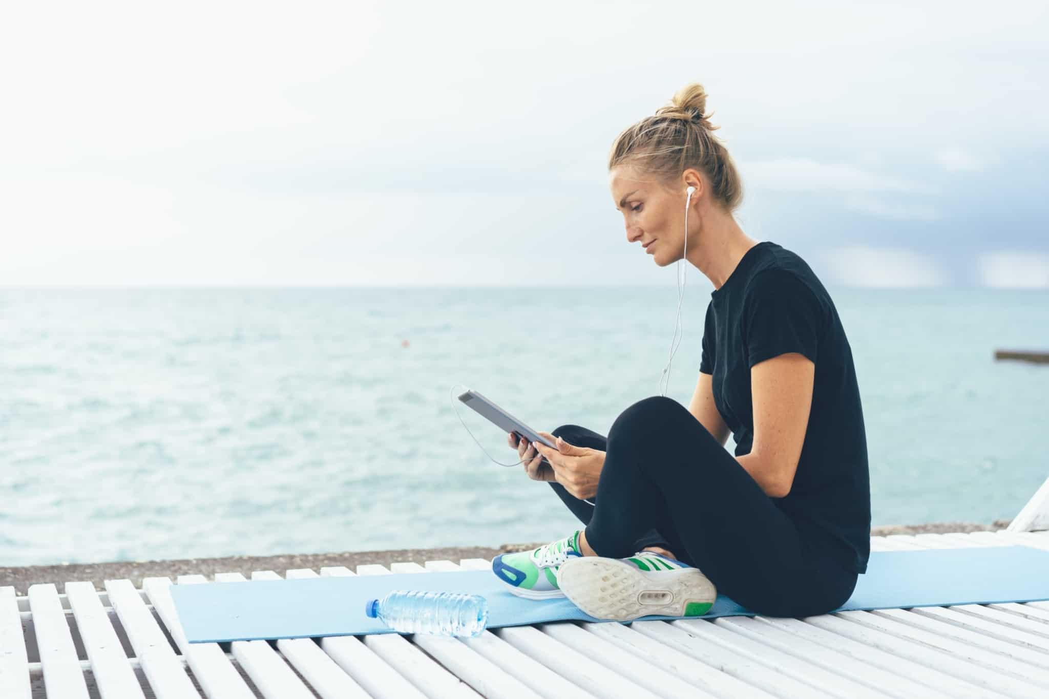 rapariga sentada num tapete de yoga a olhar para o tablet