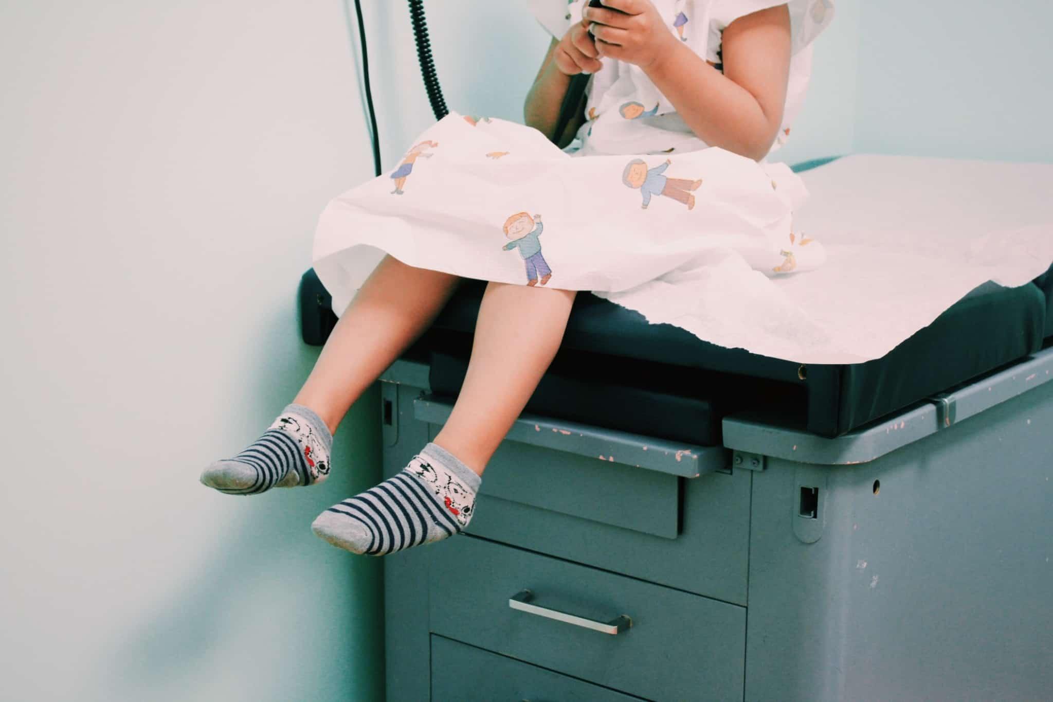 criança sentada à espera do médico