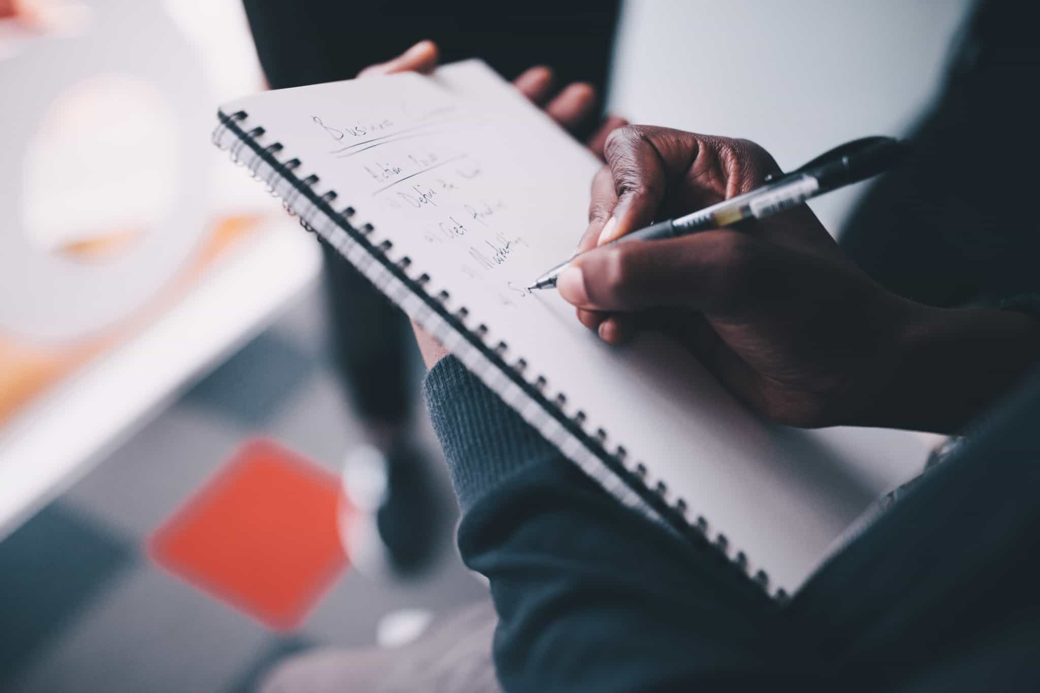 pessoa a escrever ideias de uma reunião