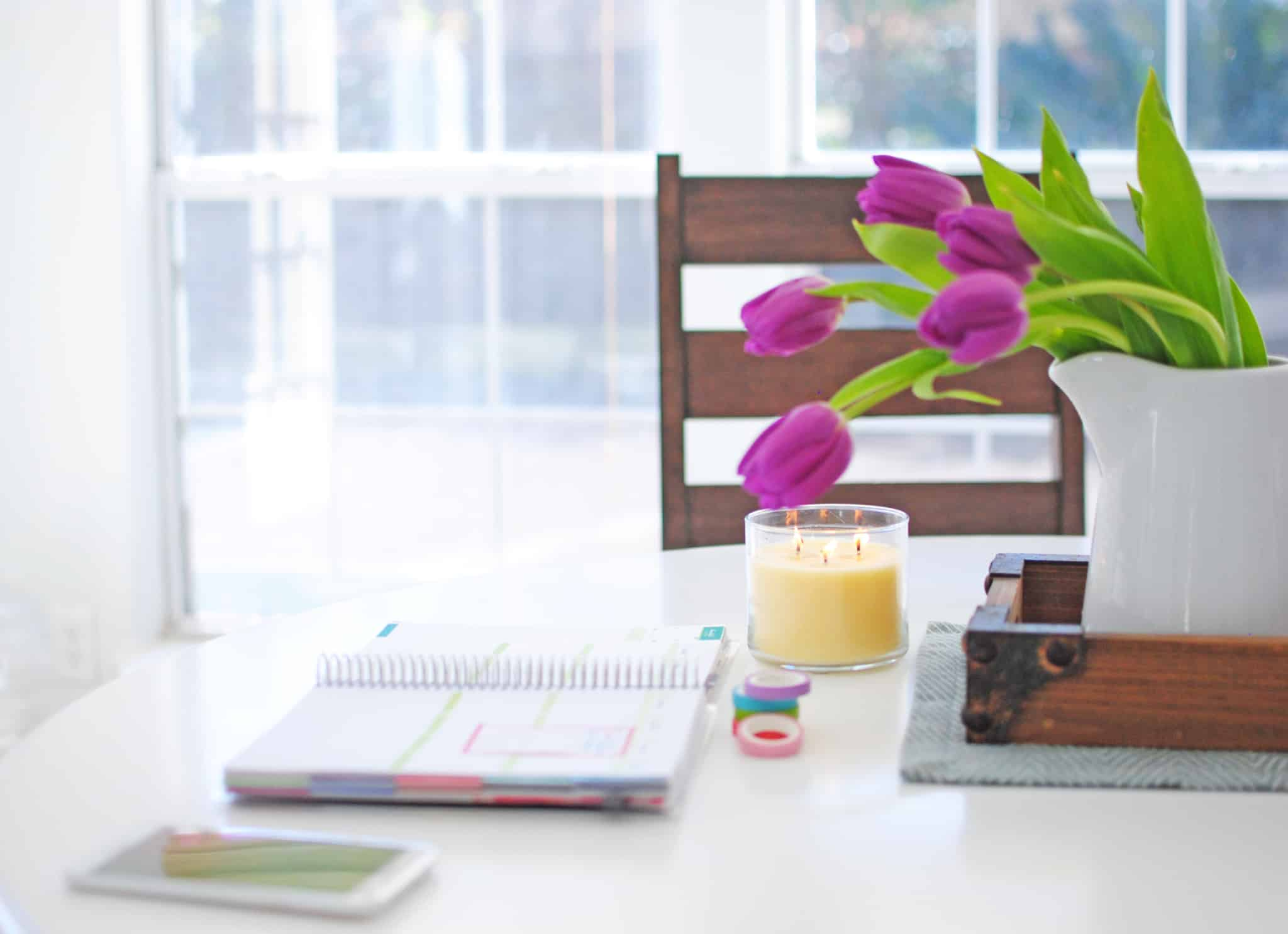 caderno em cima da mesa com vaso de flores ao lado