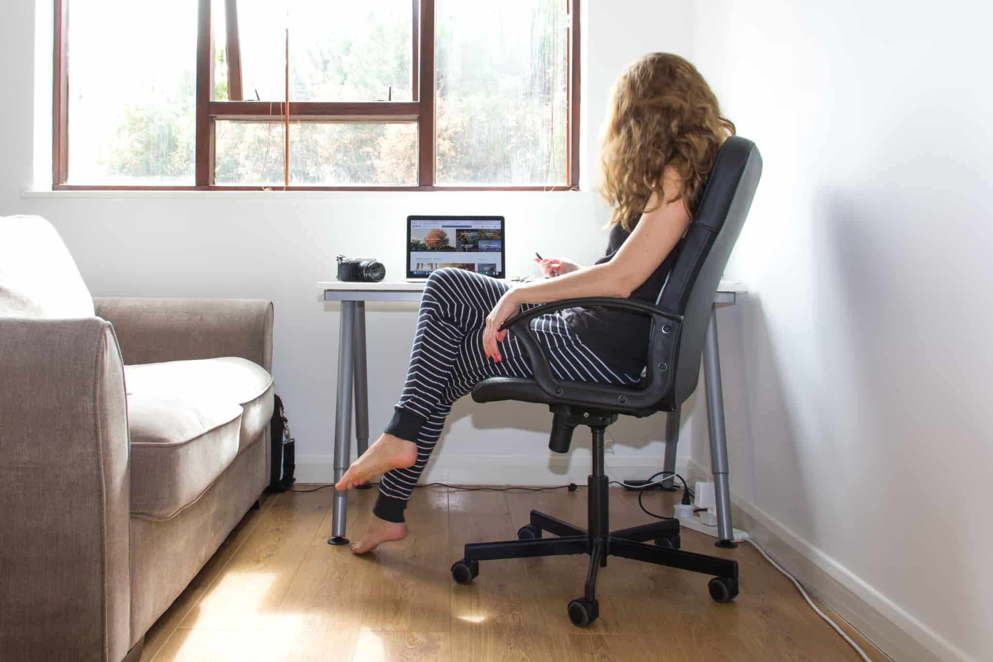 rapariga a trabalhar à secretária ao lado do sofá