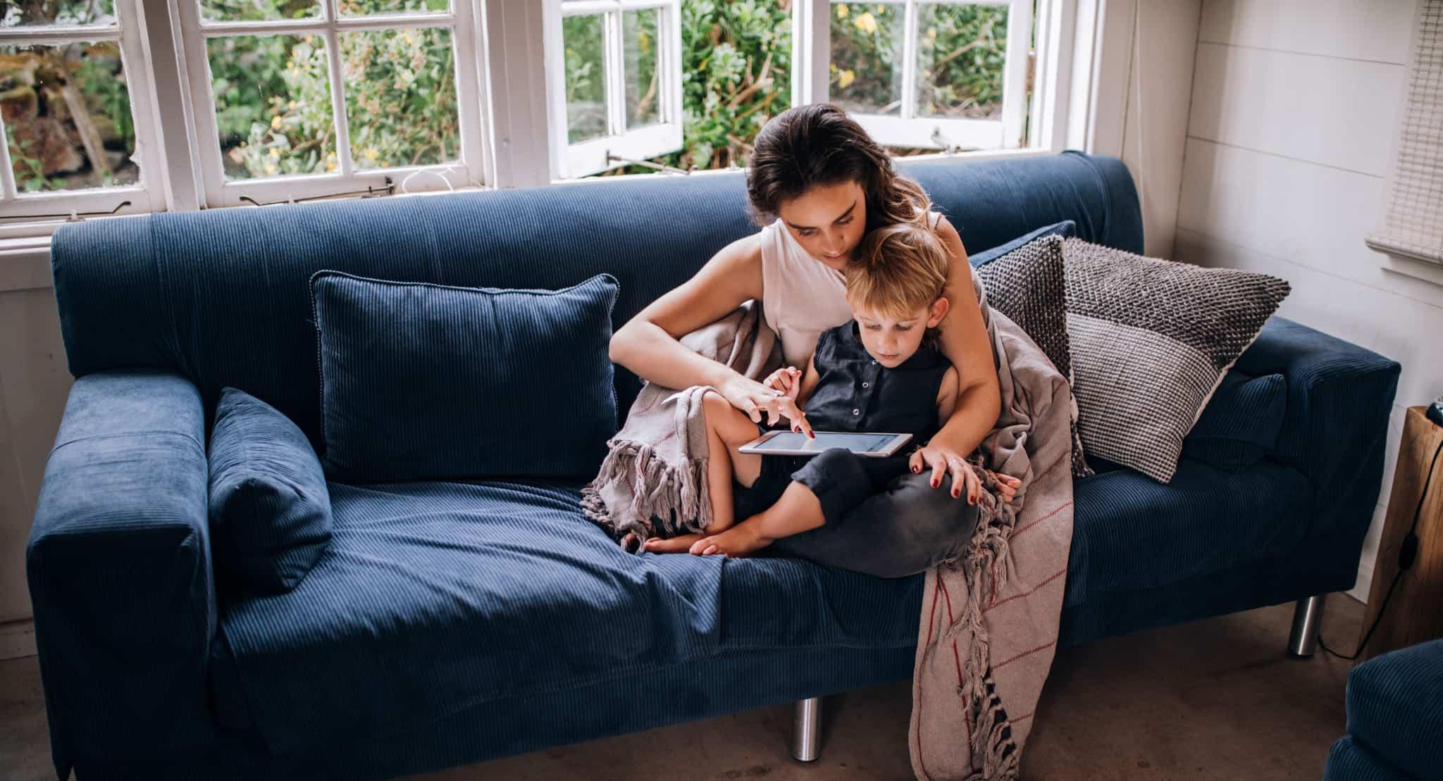 mãe com filho ao colo sentados no sofá