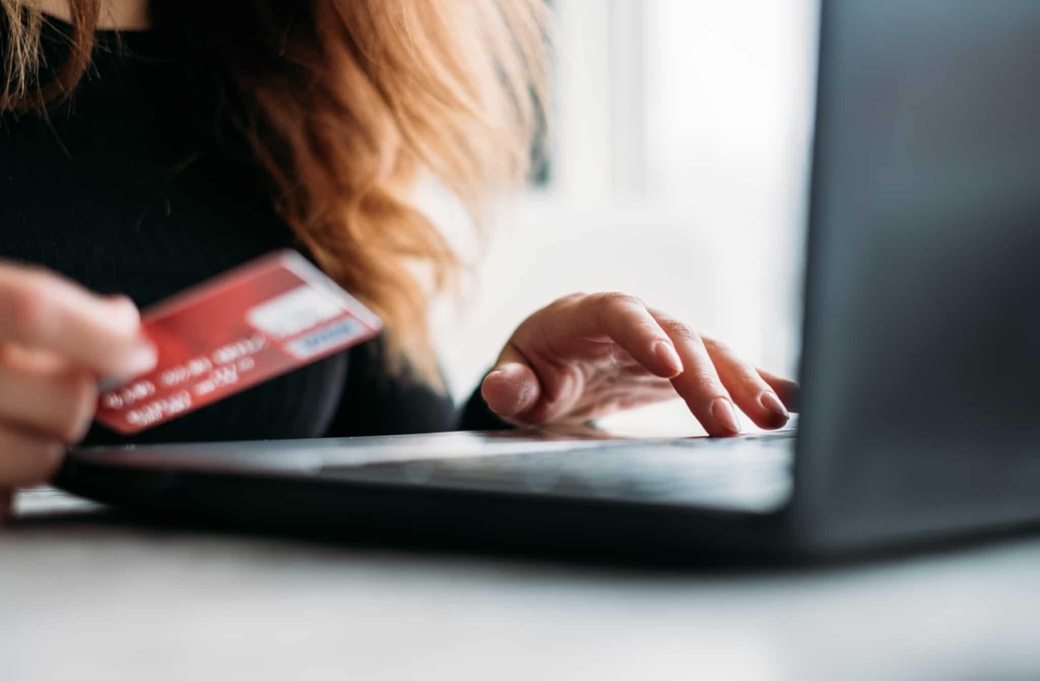 rapariga a utilizar o computador e a segurar um cartão de crédito para fazer compras em e commerce