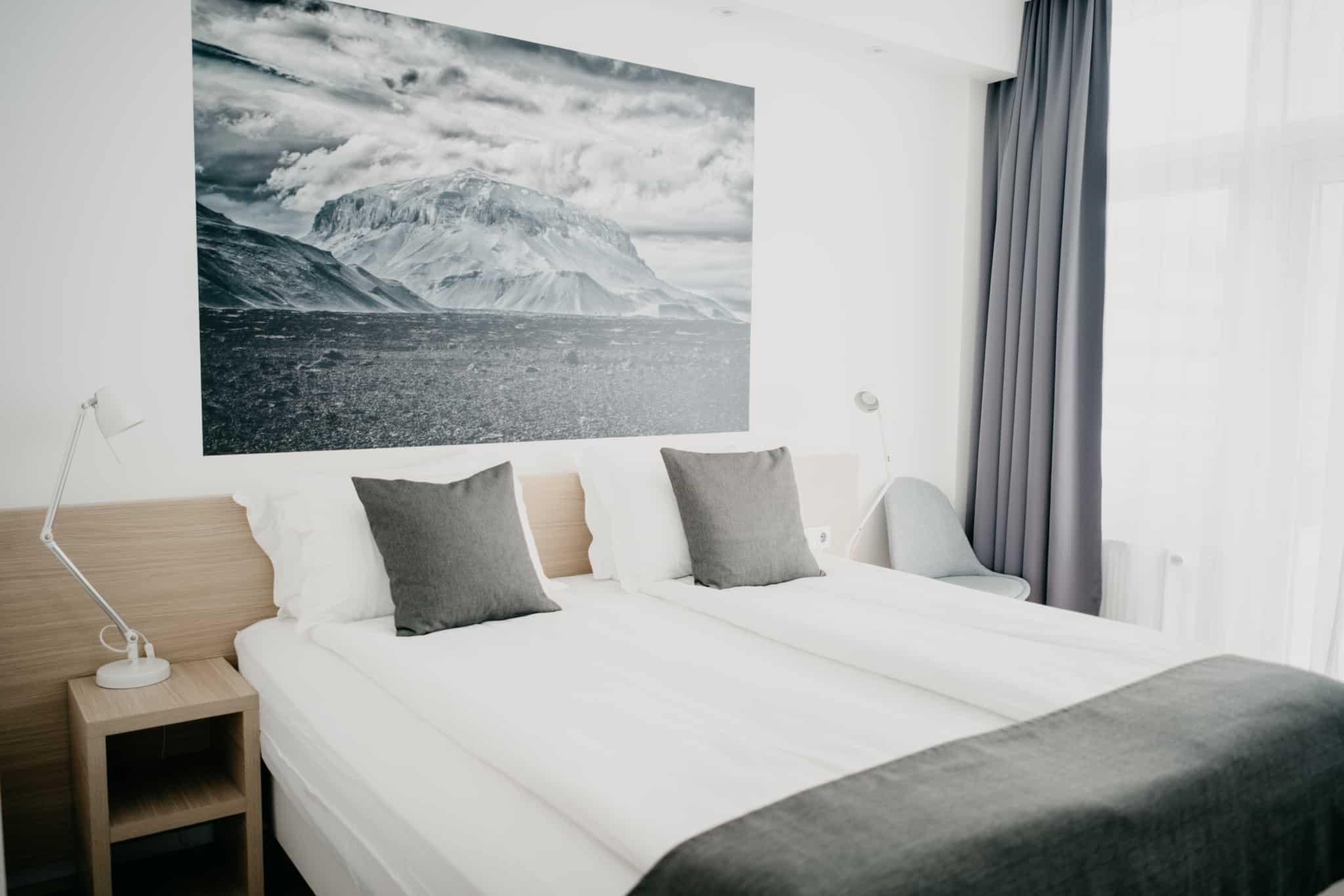 quarto de hotel com duas camas um quadro com um iceberg na parede