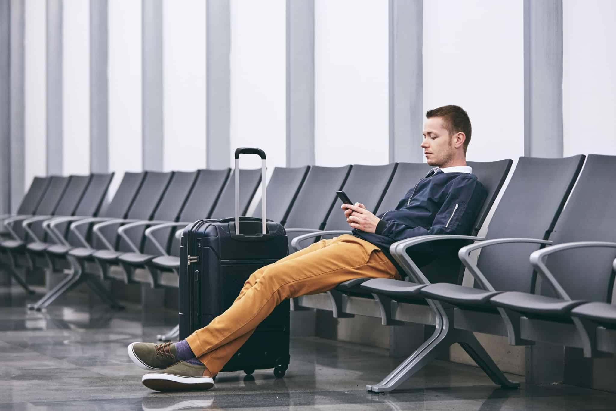 homem sentado na sala de espera de um aeroporto