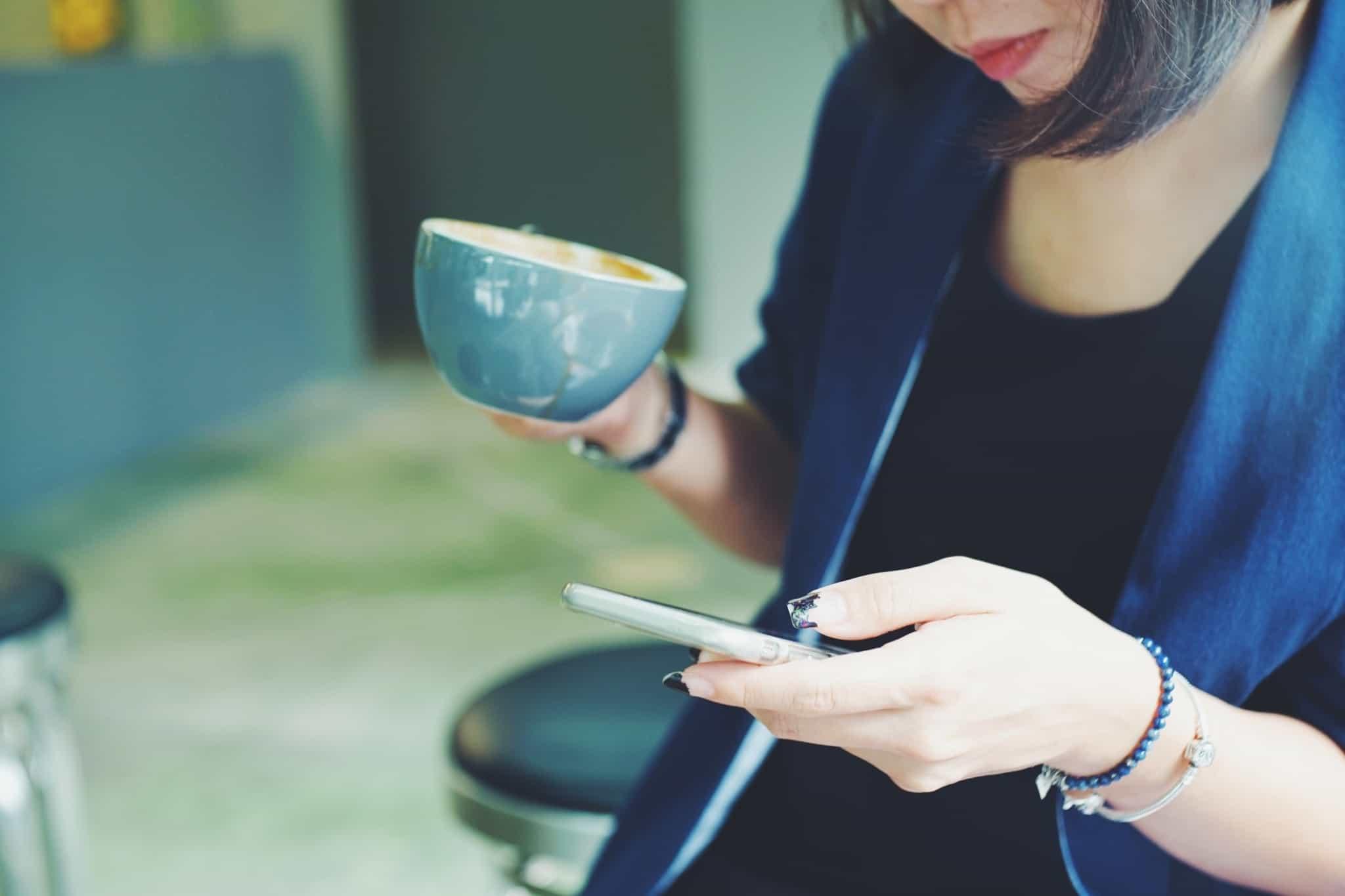 mulher com uma chávena de café e a mexer no telemóvel