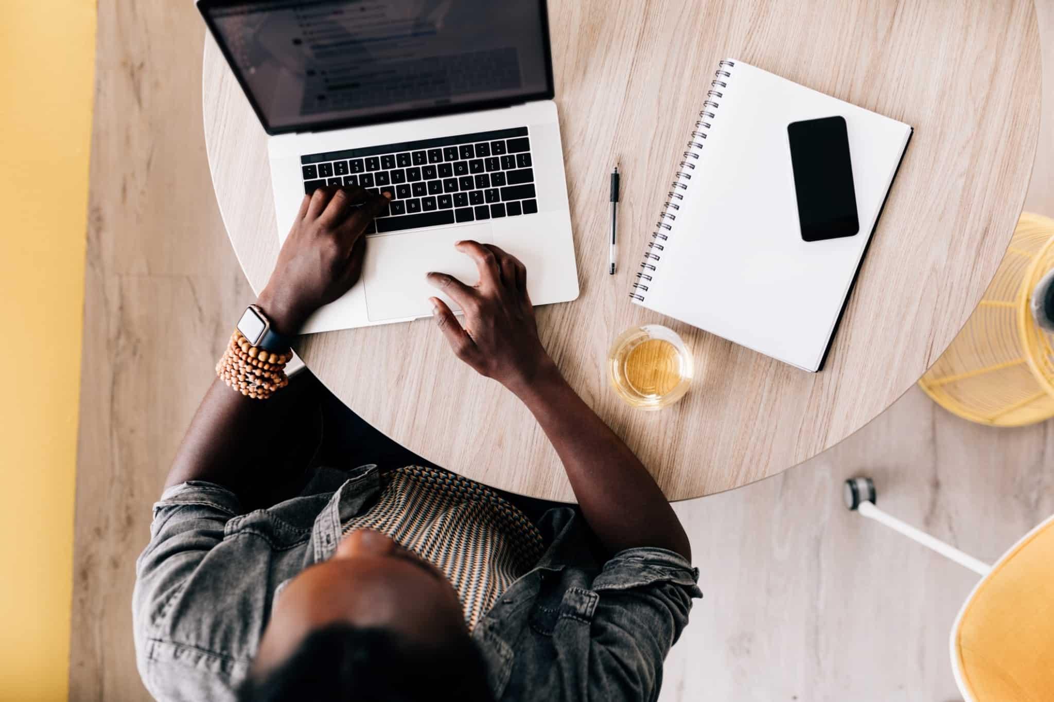 pessoa a trabalhar numa mesa redonda com portátil e bloco de notas