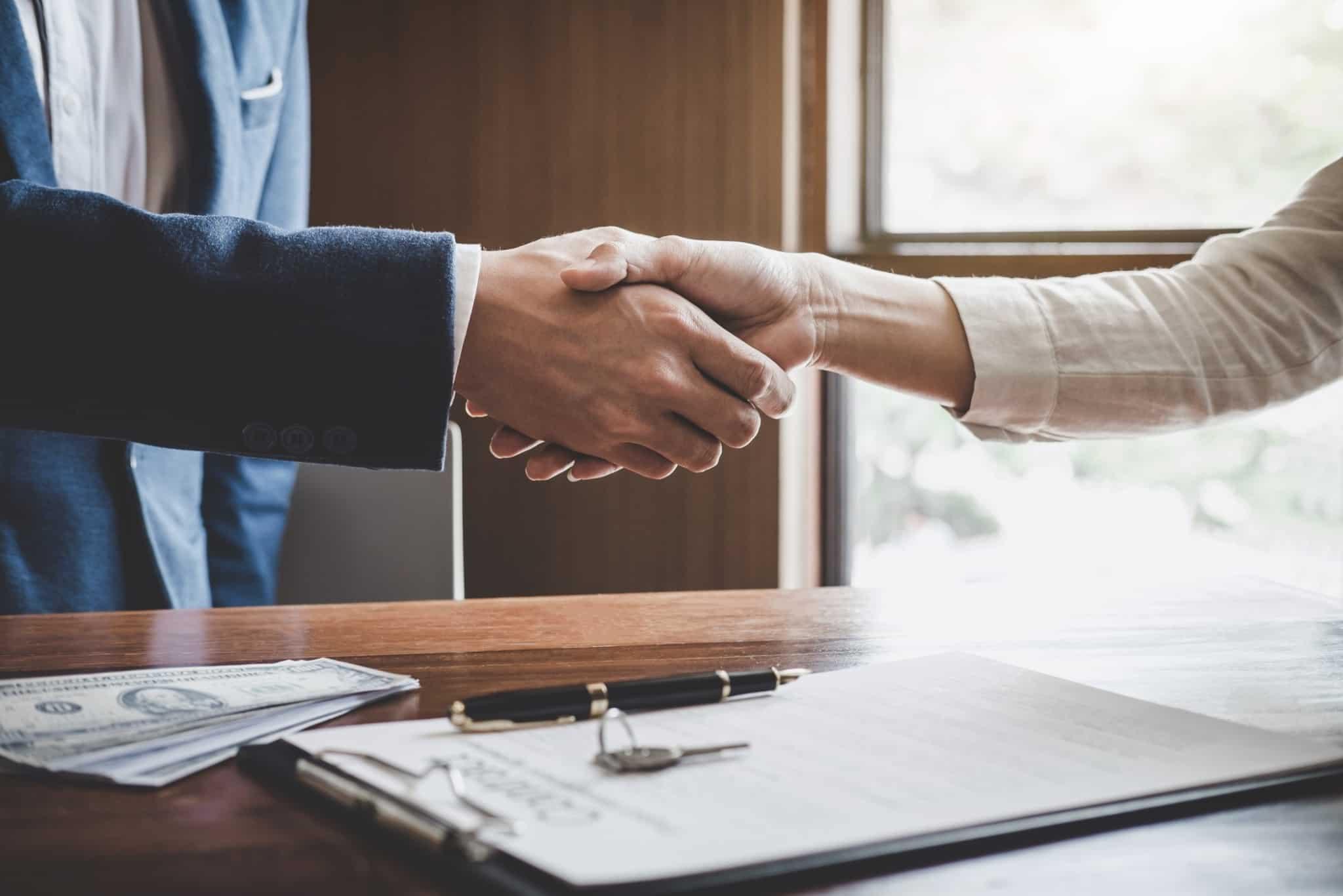 agente imobiliário a fechar um contrato com um aperto de mão