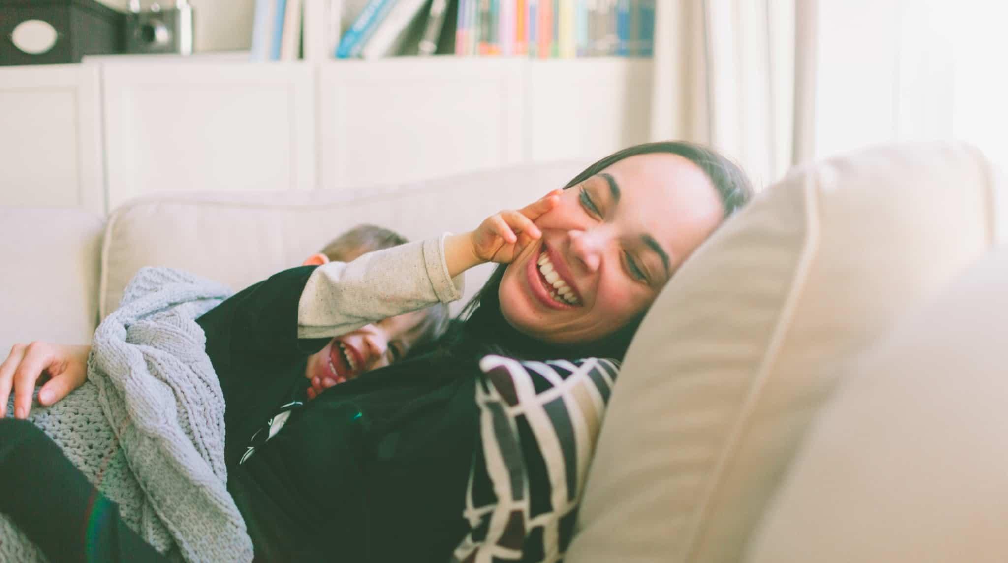 Mãe e filho no sofá a sorrir