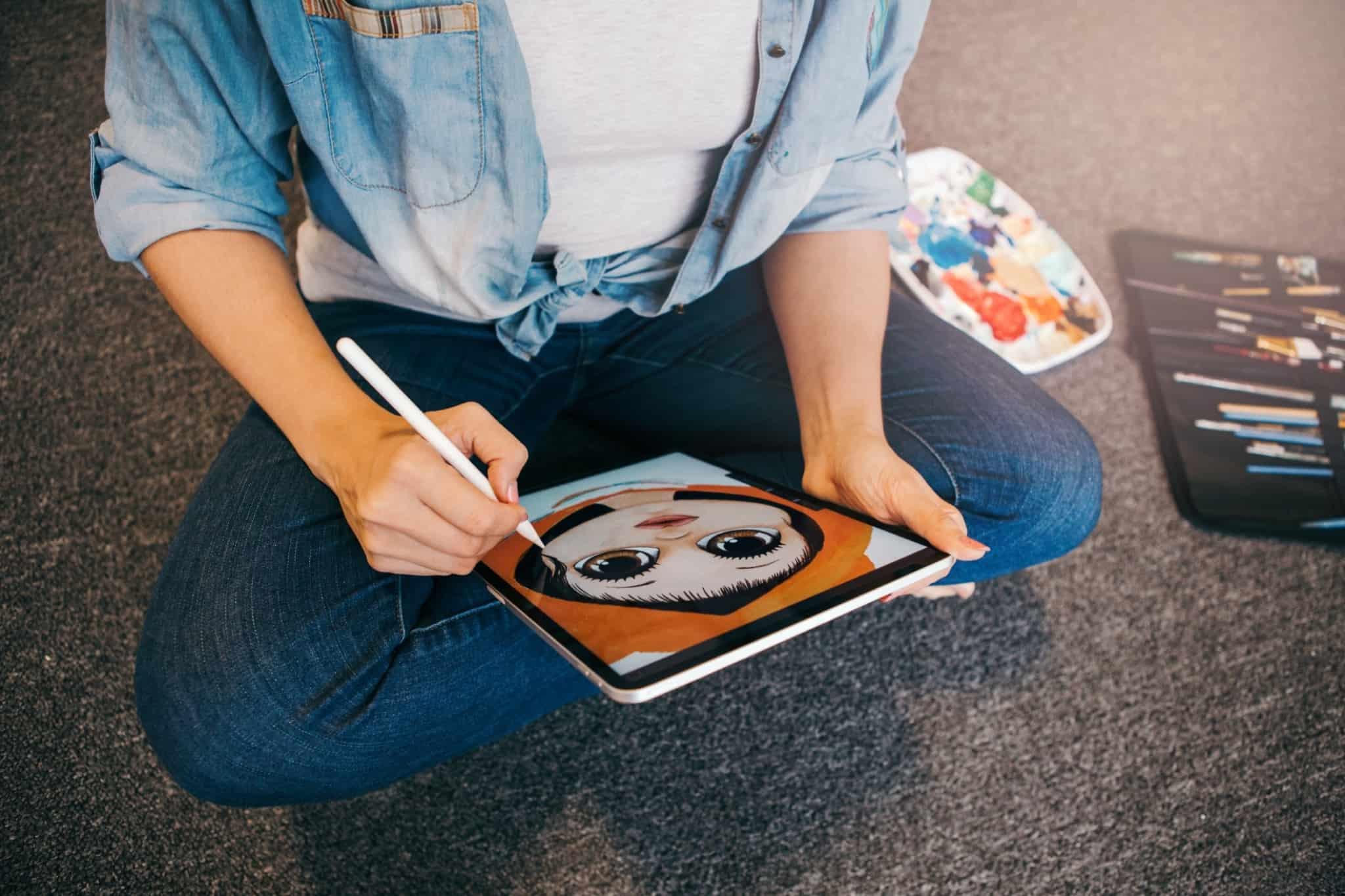 mulher designer a desenhar no tablet uma cara
