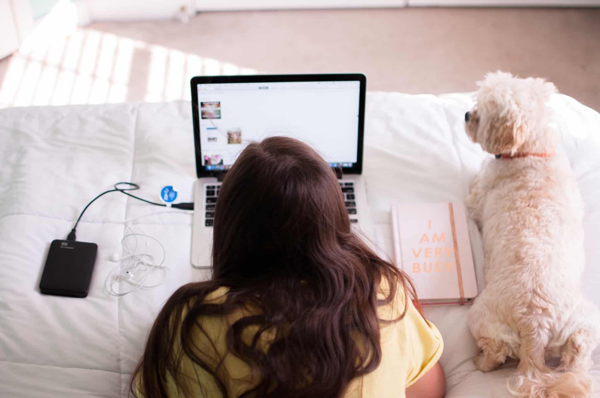 rapariga deitada na cama com o computador aberto e o cão ao lado