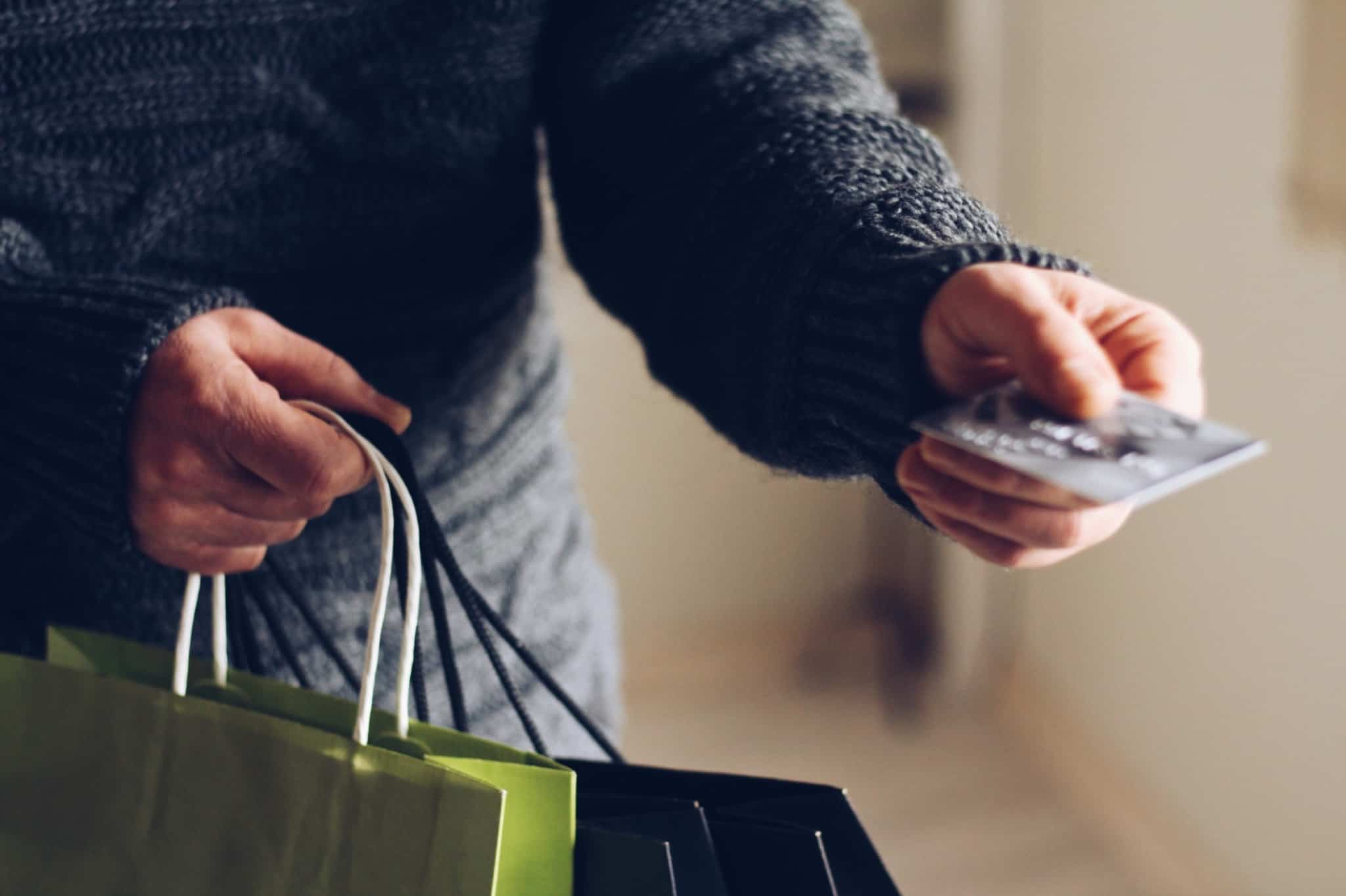 pessoa entrega cartao de pagamentos com sacos de compras