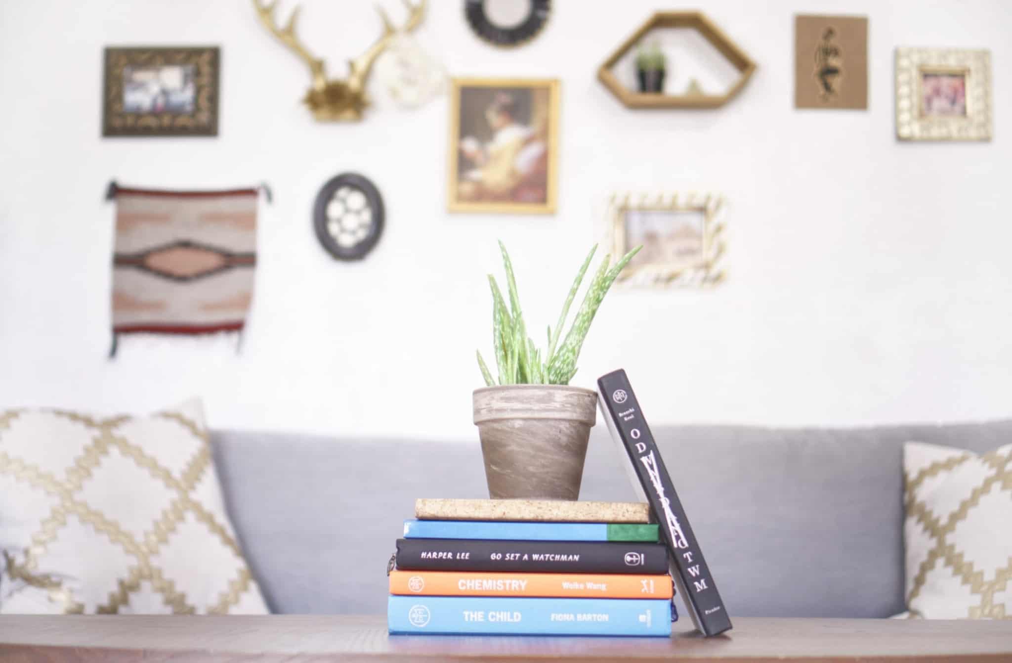 mesa central com livros e uma parede com vários quadros