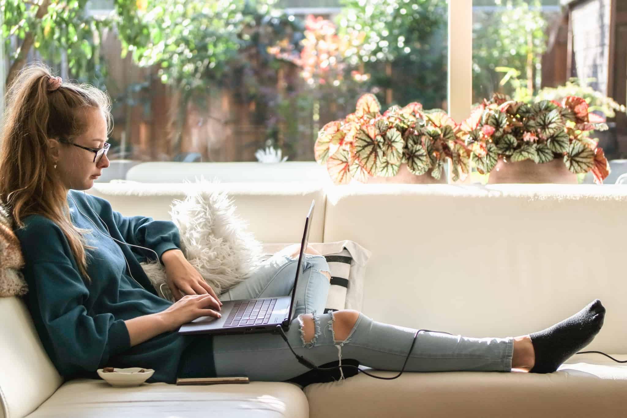 rapariga a estudar deitada no sofá com computador ao colo