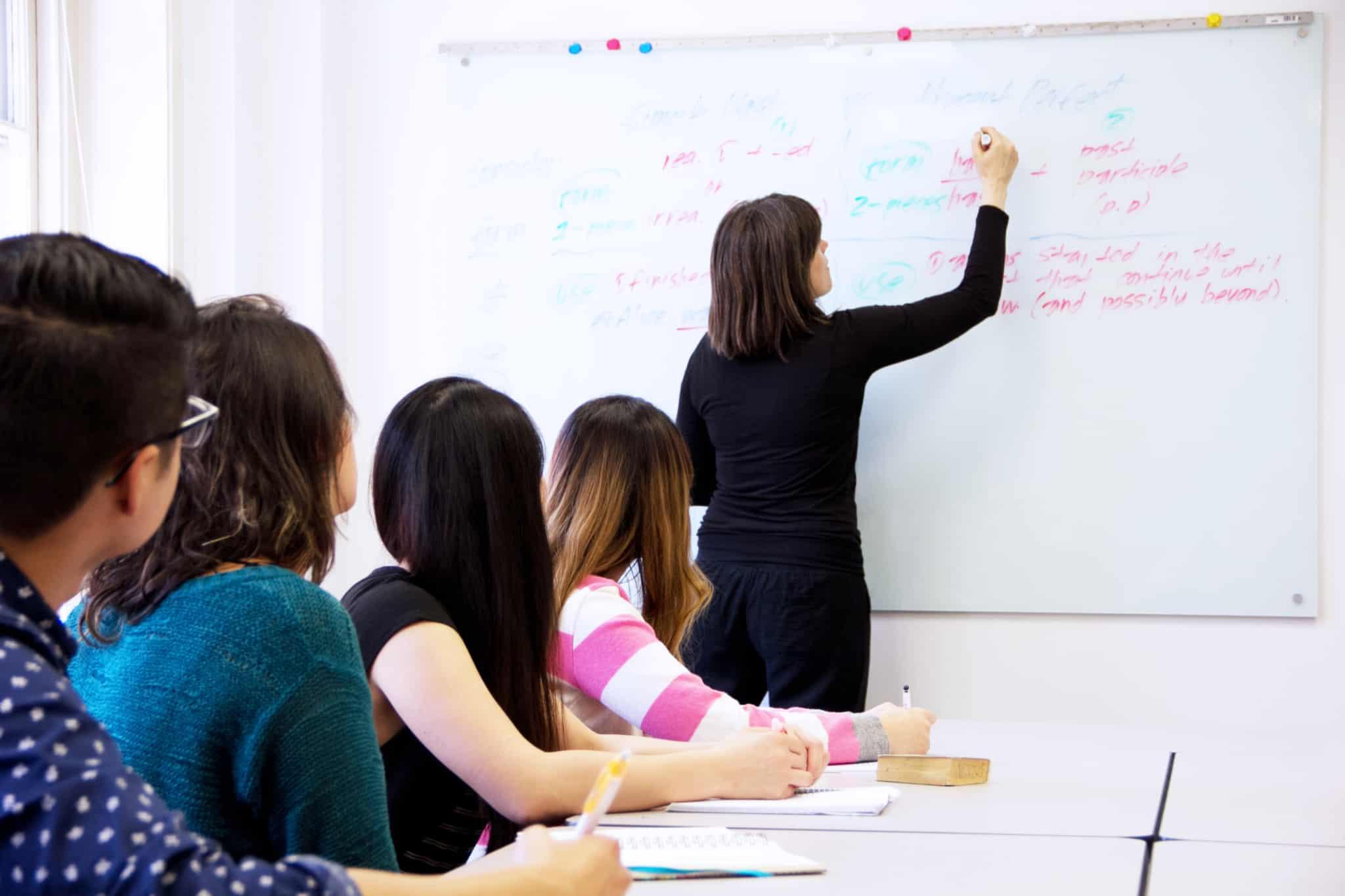 professora a escrever num quadro branco com 4 alunos a ver