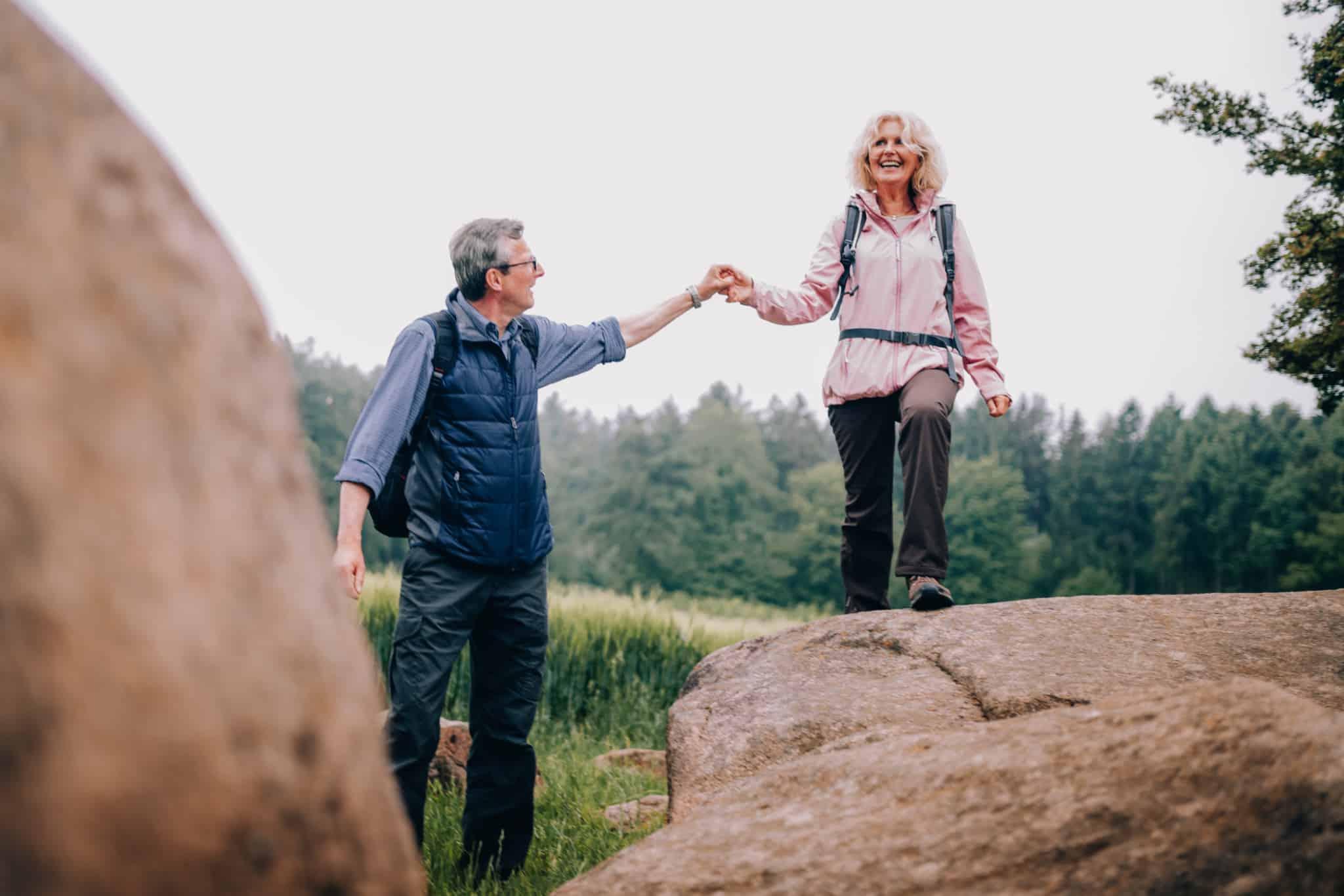 casal de 50 anos a passear em cima de rochas