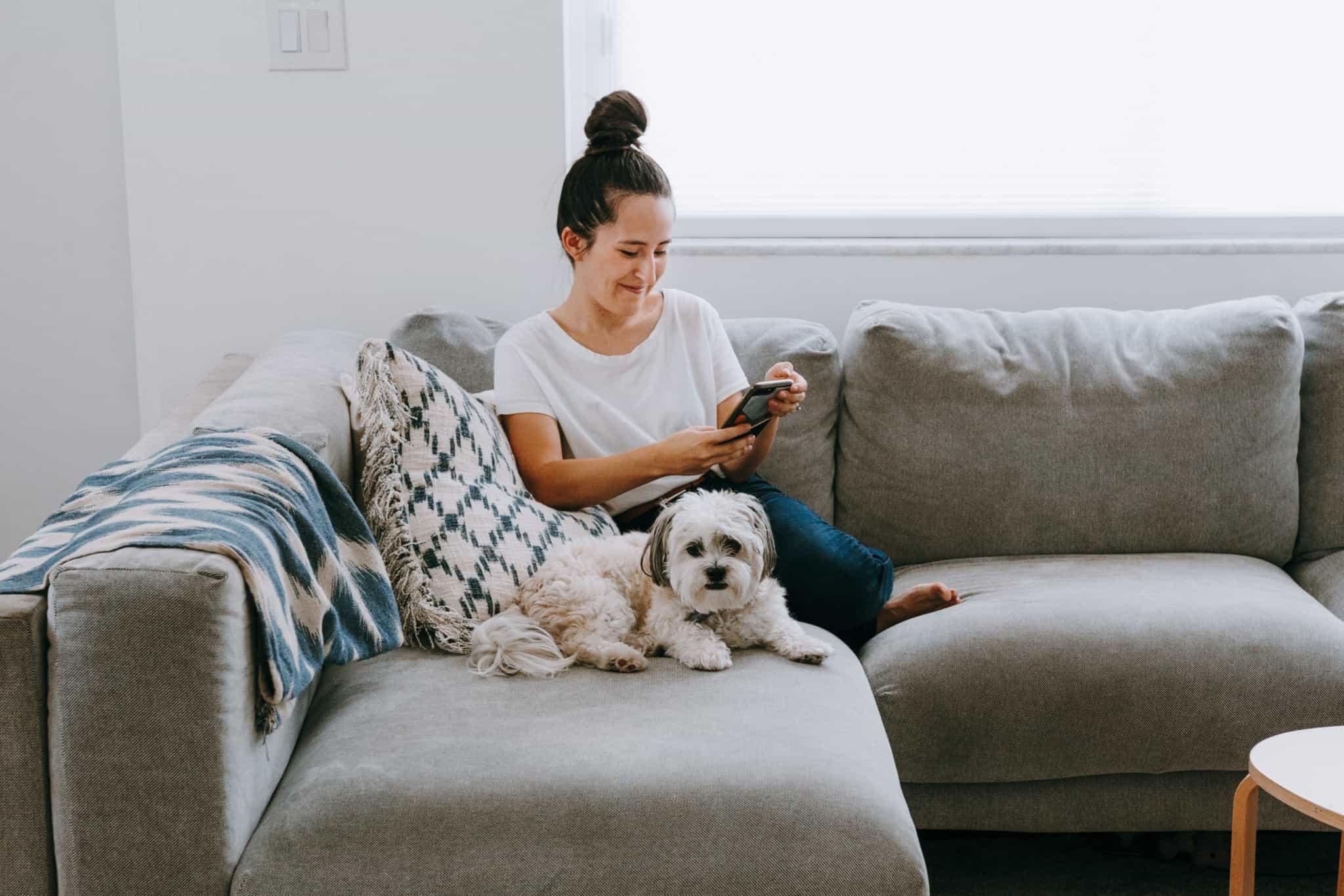 rapariga sentada no sofá a mexer no telemóvel com o cão ao lado