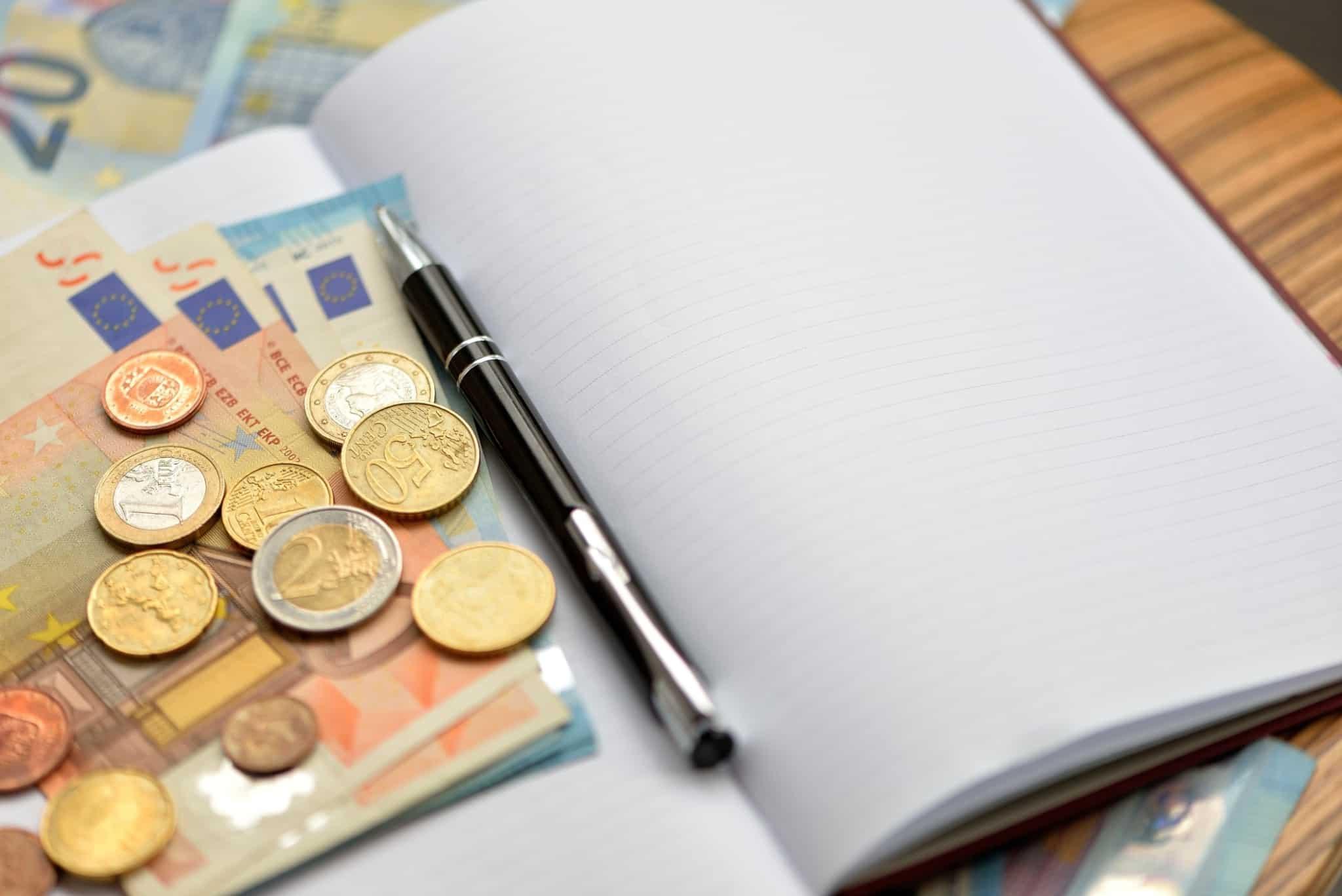 Bloco de notas com uma caneta e dinheiro em cima