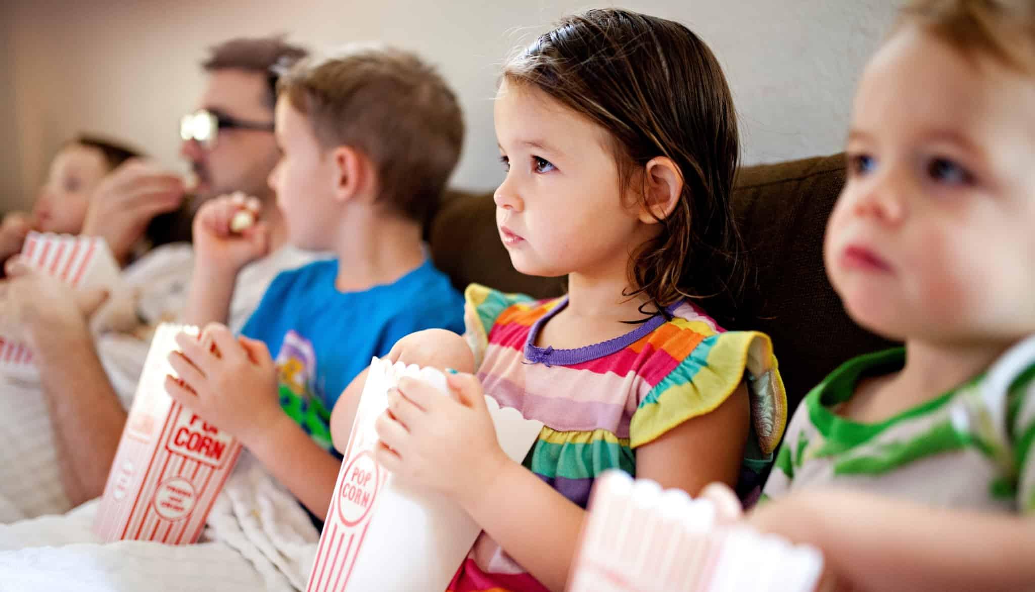 Crianças a verem um filme e a comerem pipocas