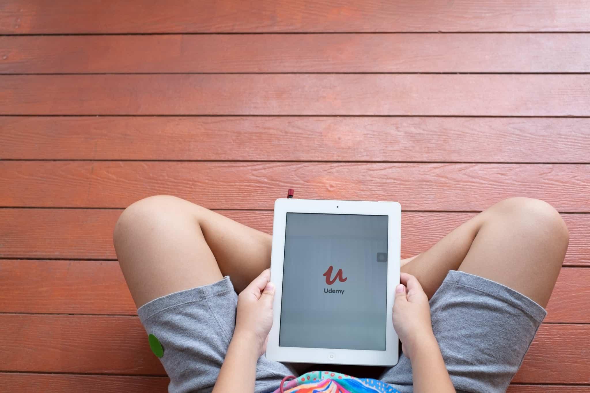 pessoa sentada com um tablet na mão com o portal udemy