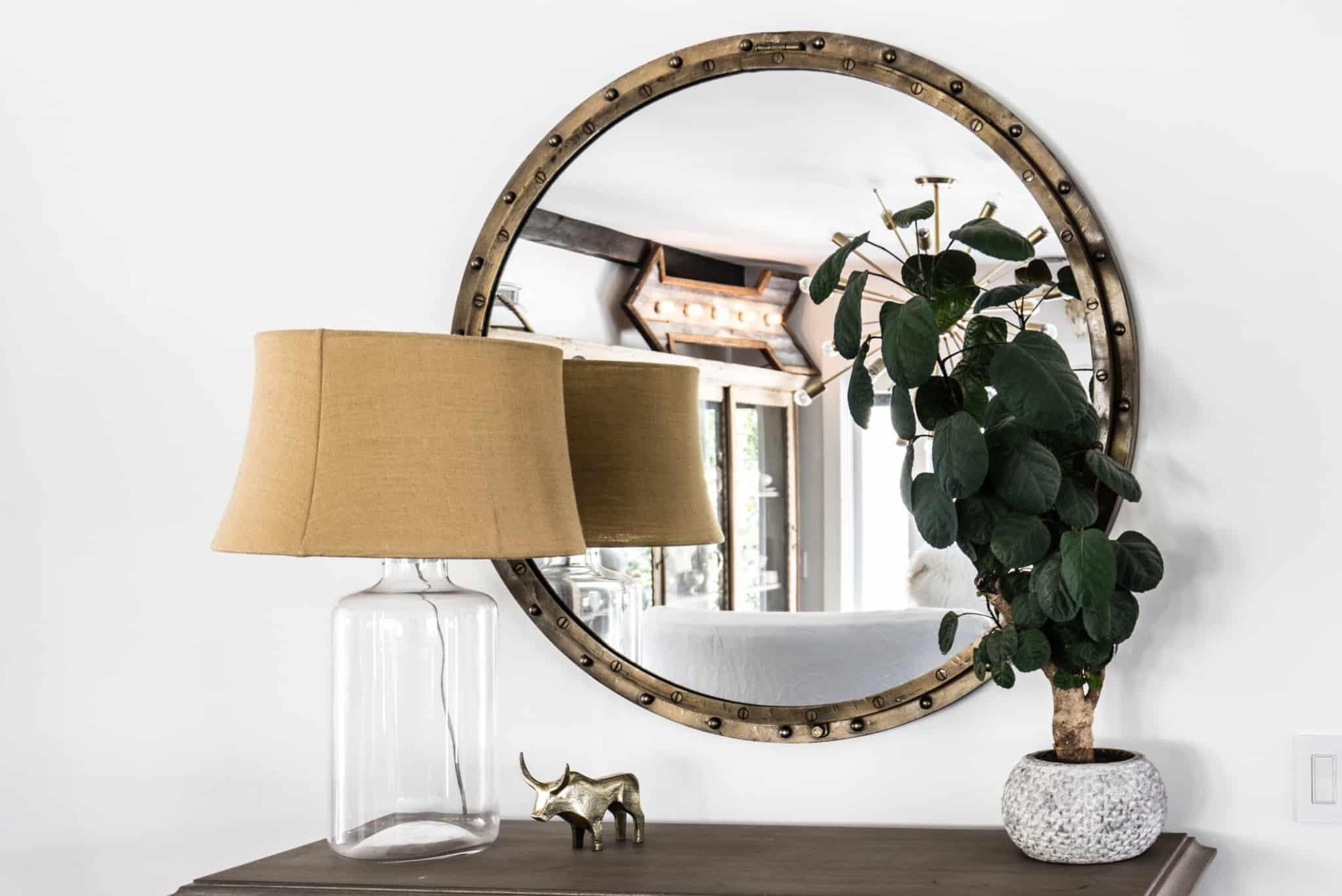 mesa de entrada com espelho redondo, uma planta e um candeeiro