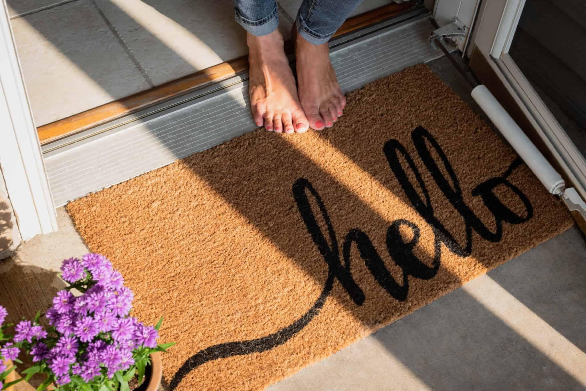 tapete de entrada de casa com a palavra hello em preto