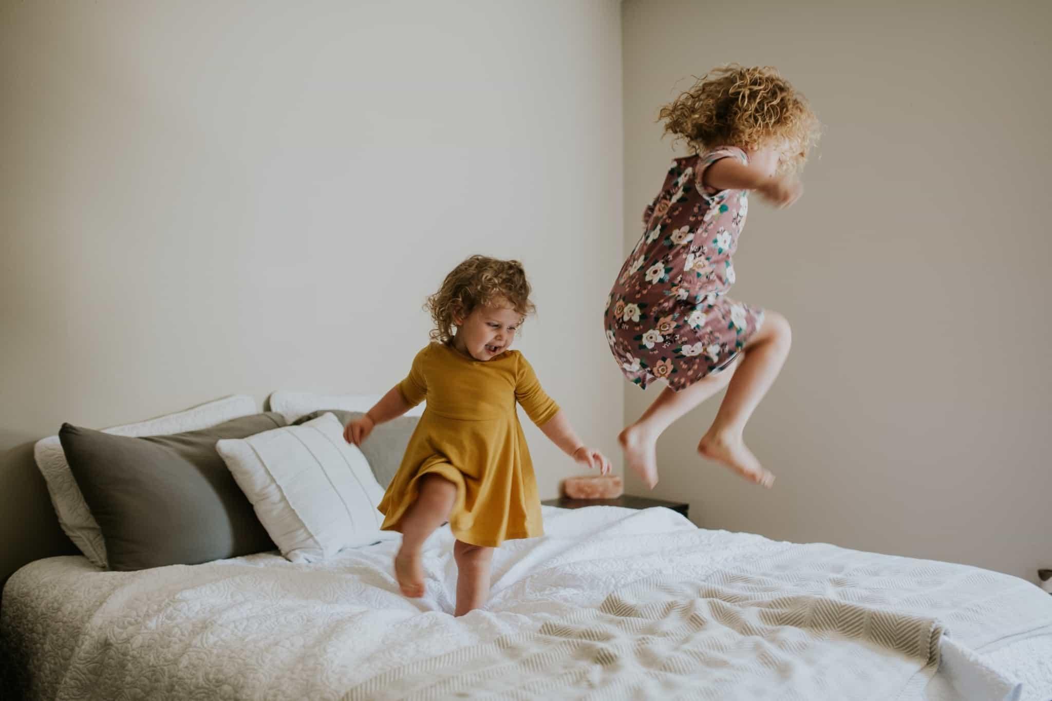 duas meninas a saltar em cima da cama