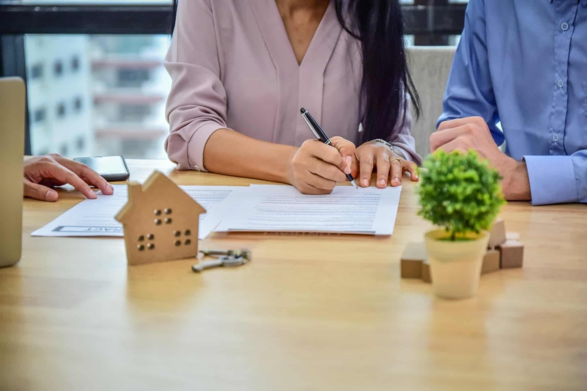 casal a assinar contrato para comprar casa
