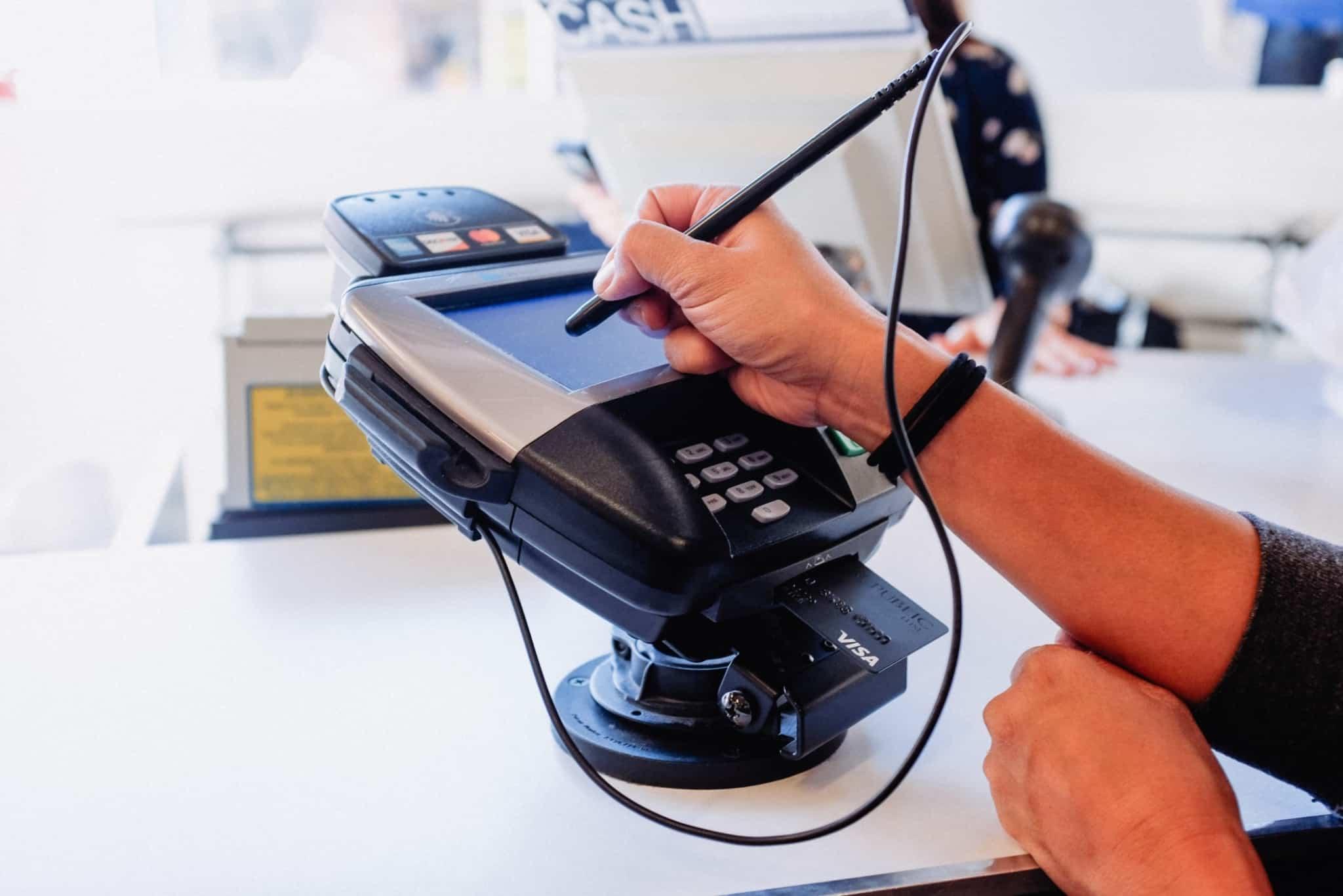 cliente a assinar num posto de pagamento de multibanco