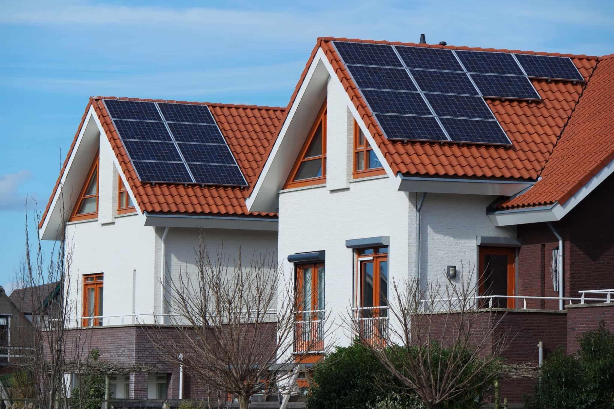 duas casas com telhados triangulares e com painéis solares