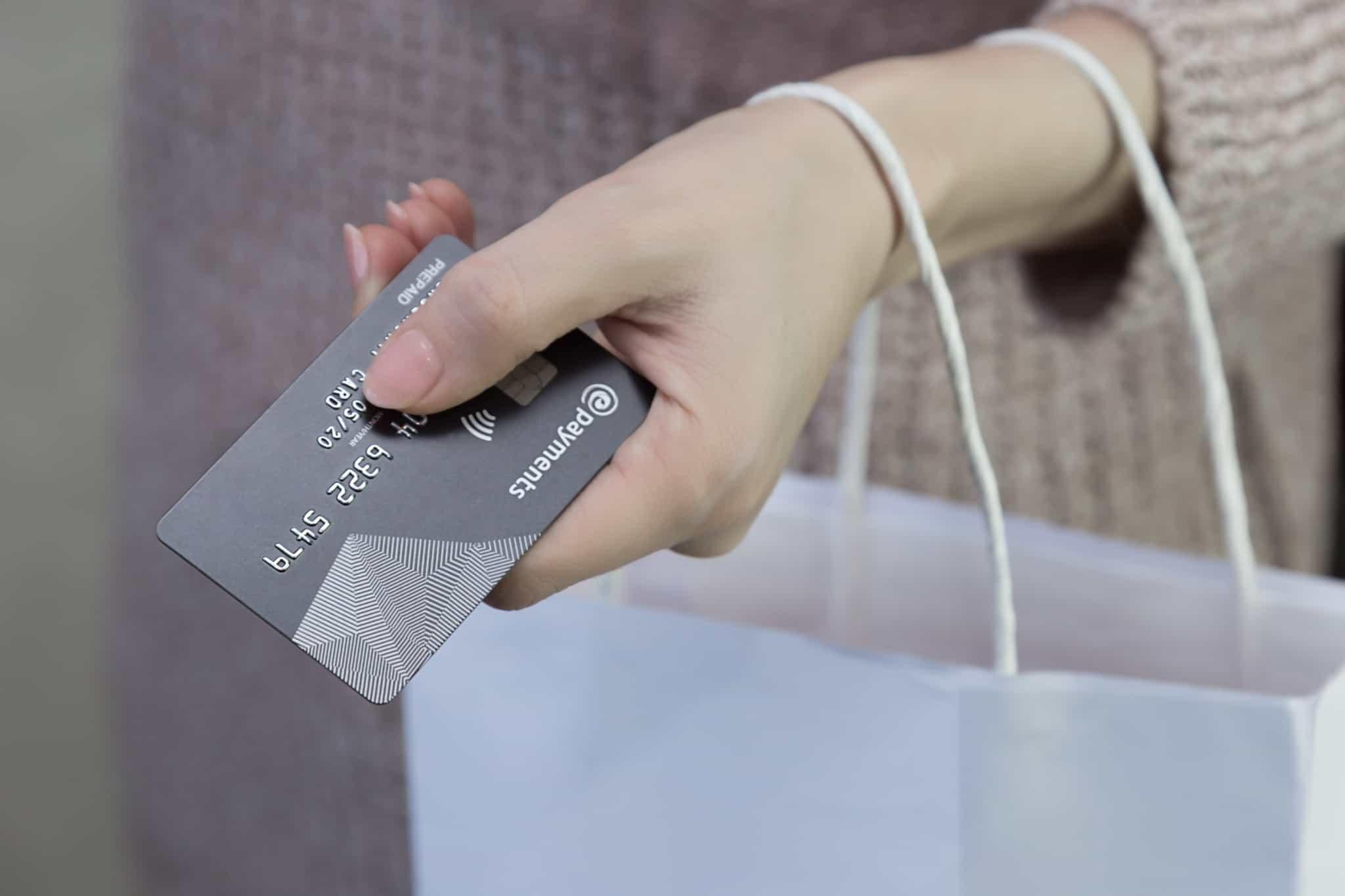 senhora a segurar o cartão de pagamentos na mão