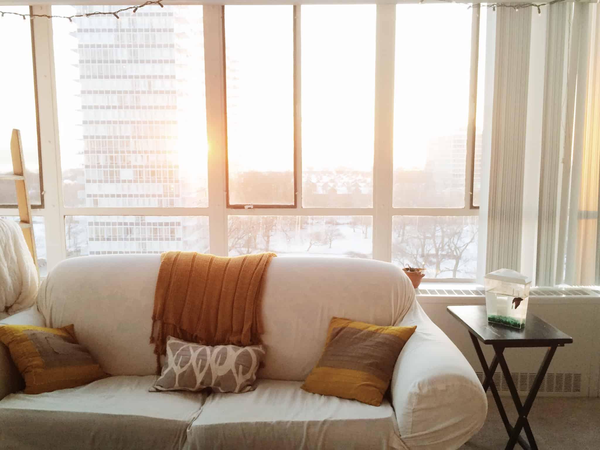 sofa branco encostado a uma janela