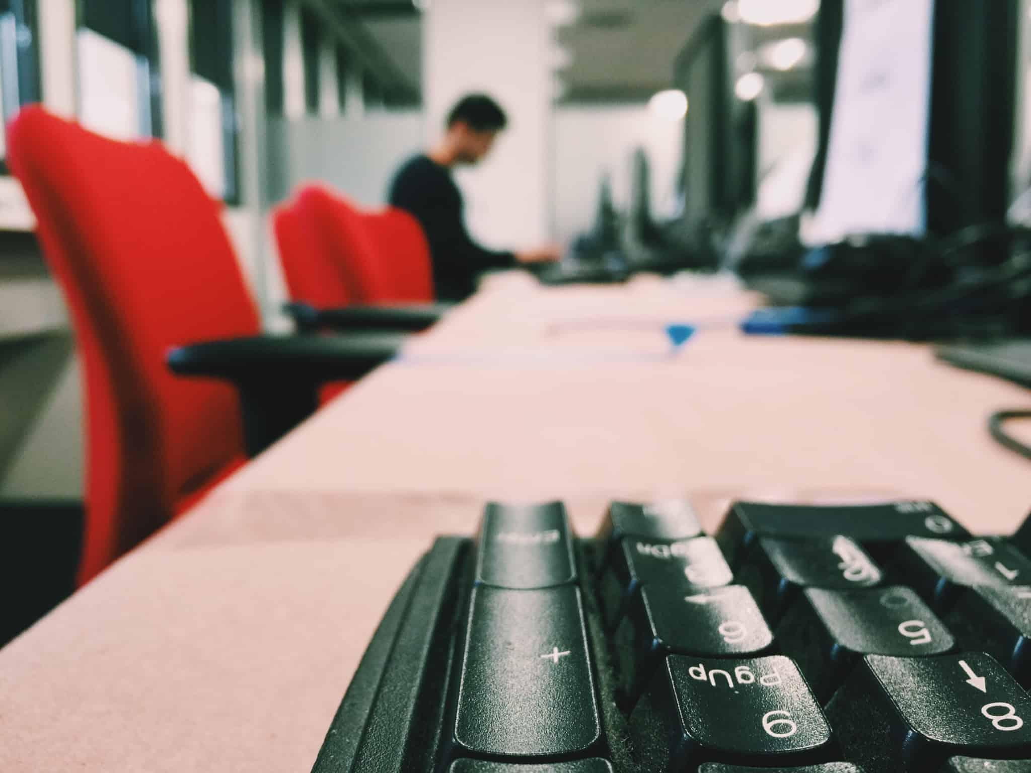 escritório com duas cadeiras vermelhas e um teclado de computador