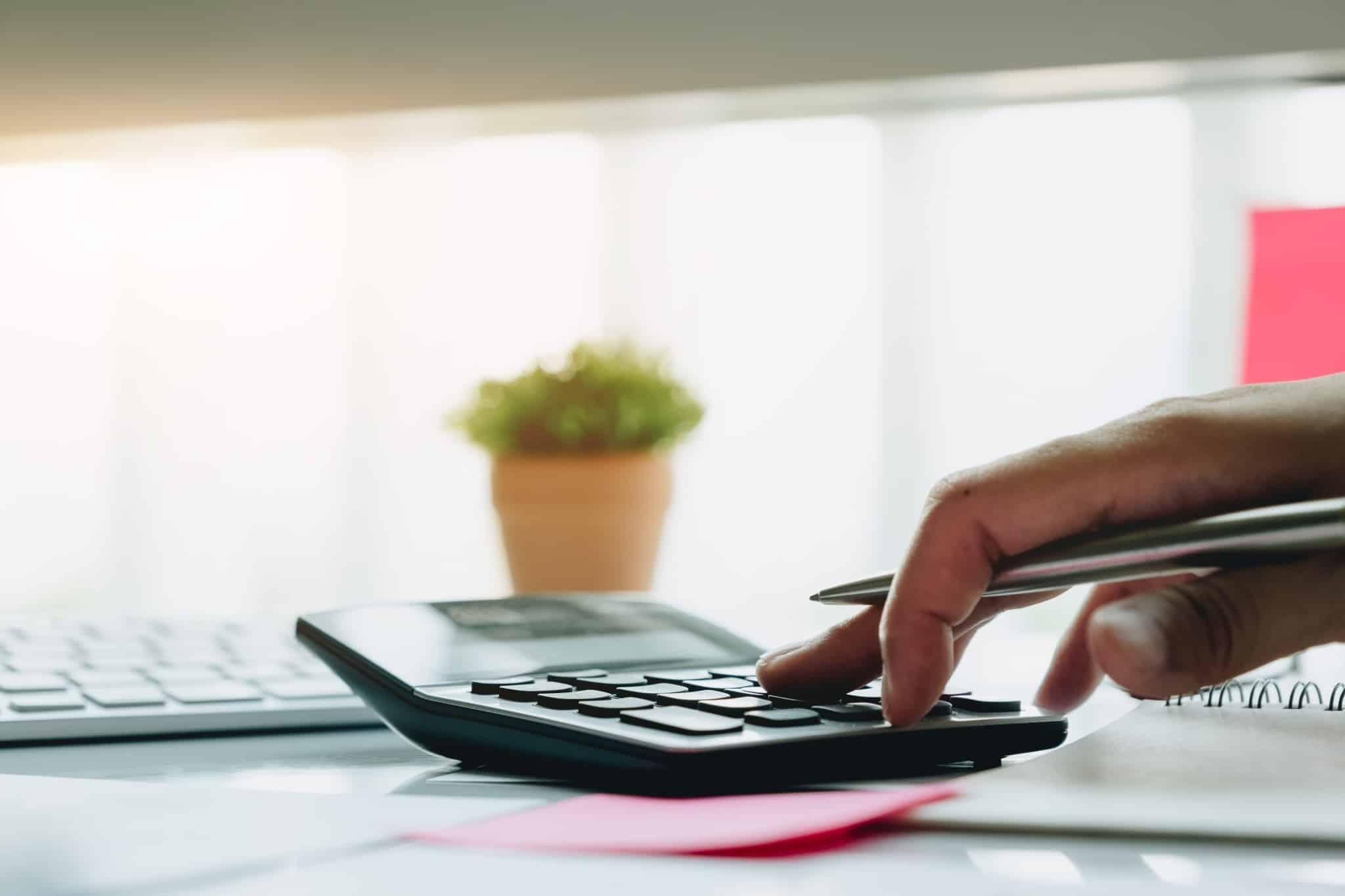 Uma caneta na mão, a fazer contas na máquina calculadora