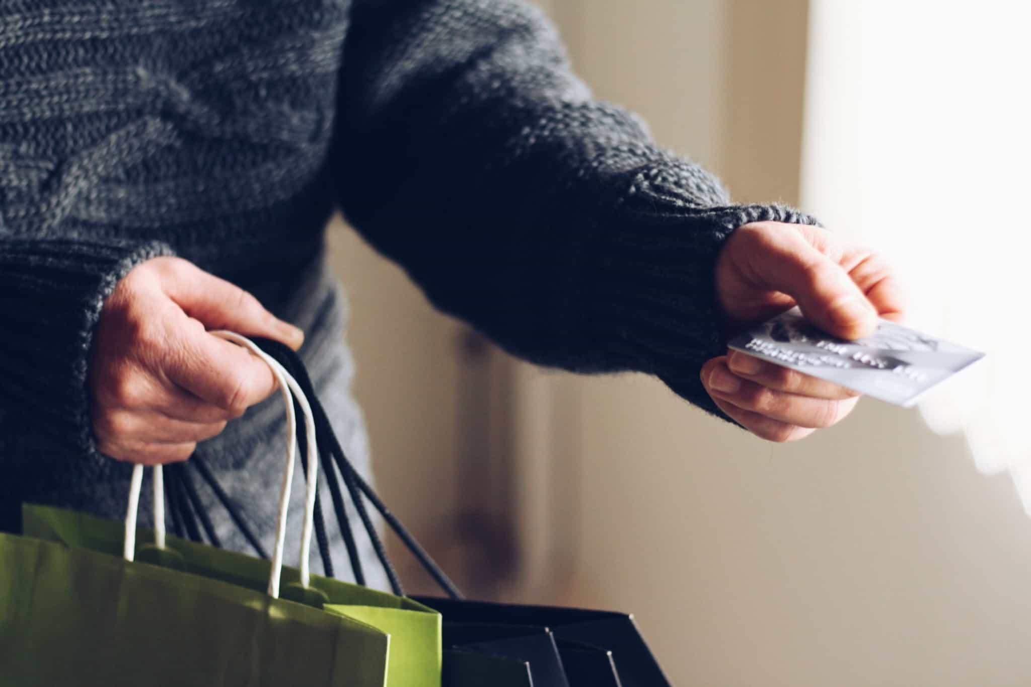 homem de camisola de lã escura a dar um cartão cinzento