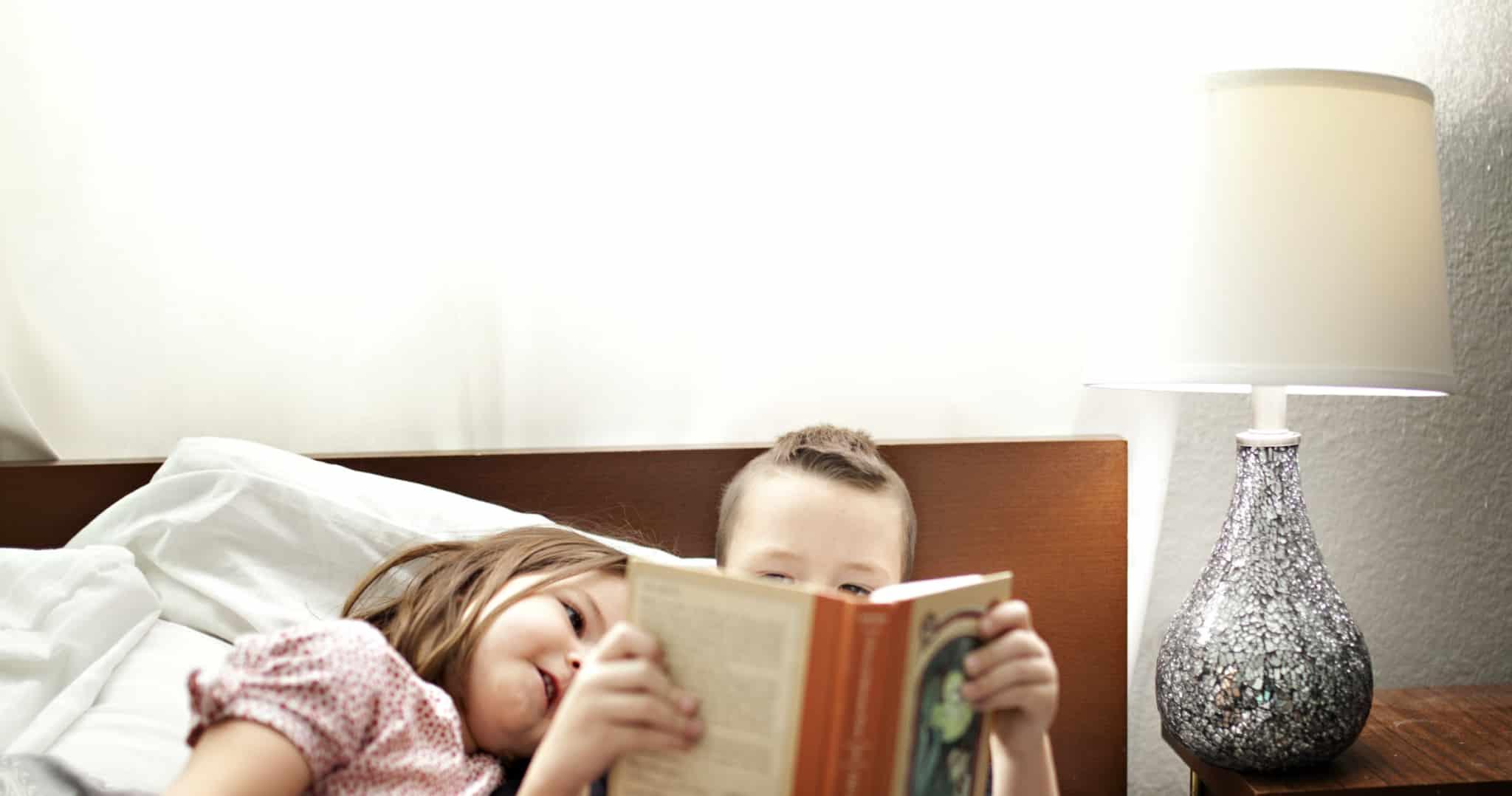 duas crianças a ler um livro ao pé de um candeeiro