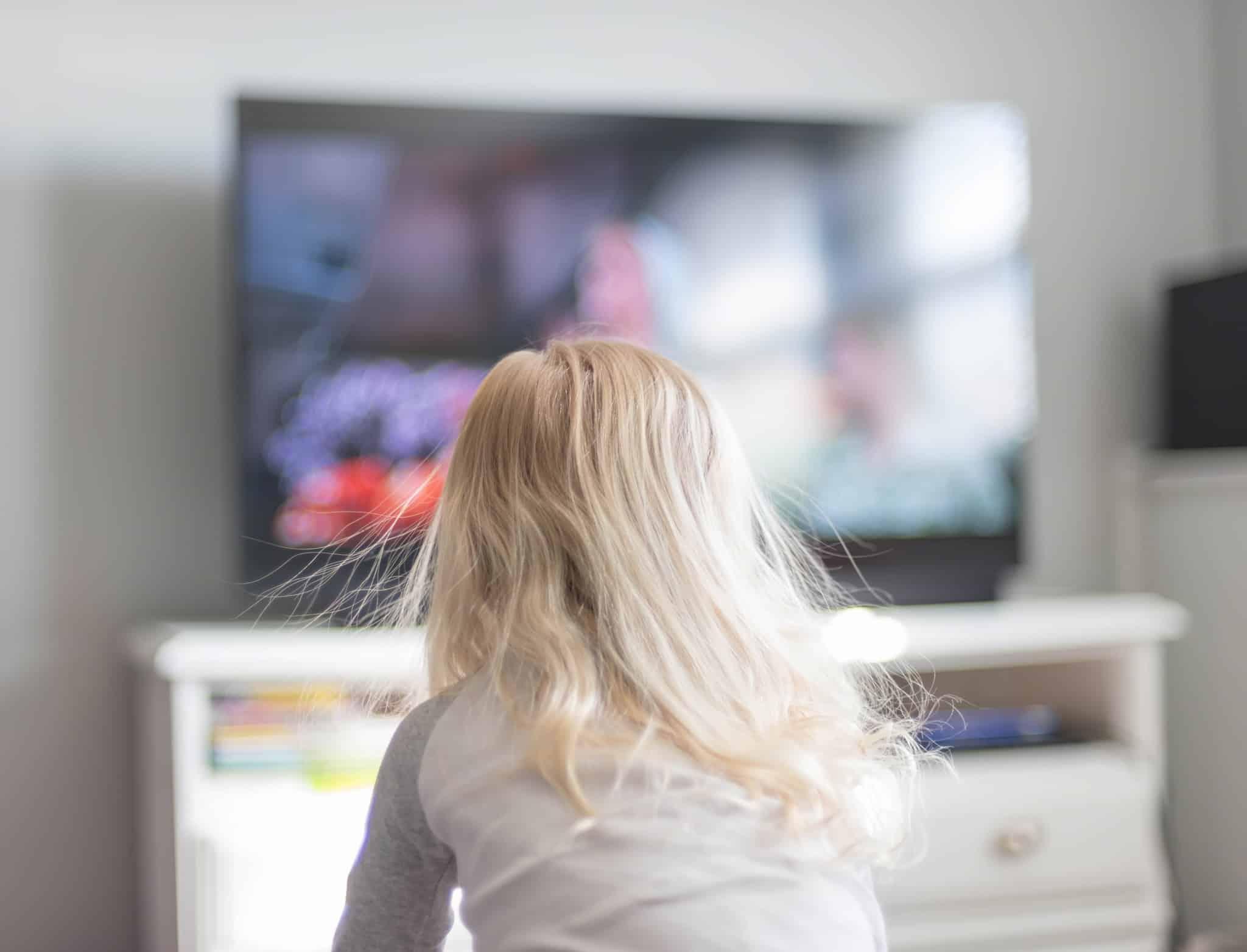 criança loira a ver televisão
