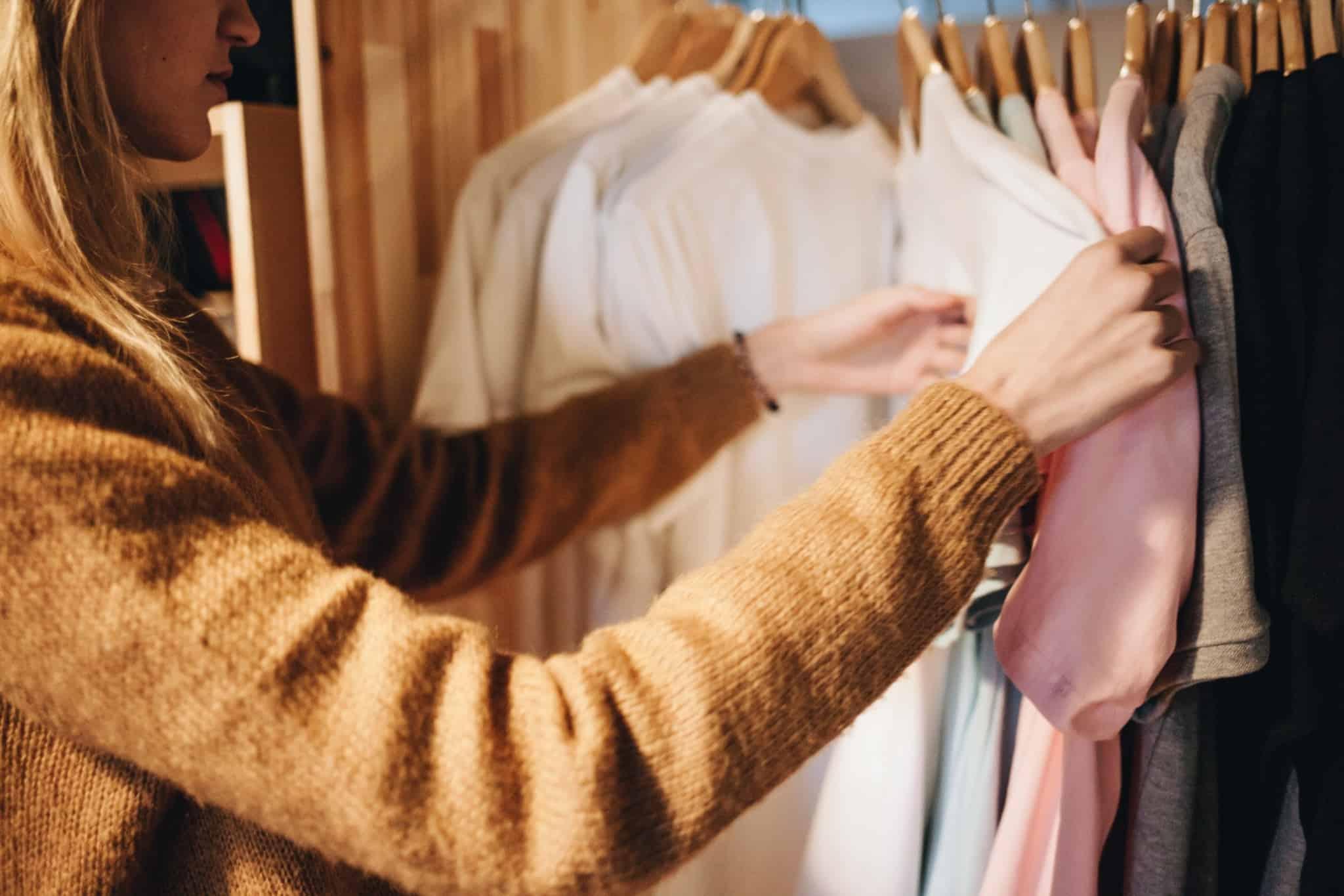 mulher a escolher tshirts numa loja de roupa