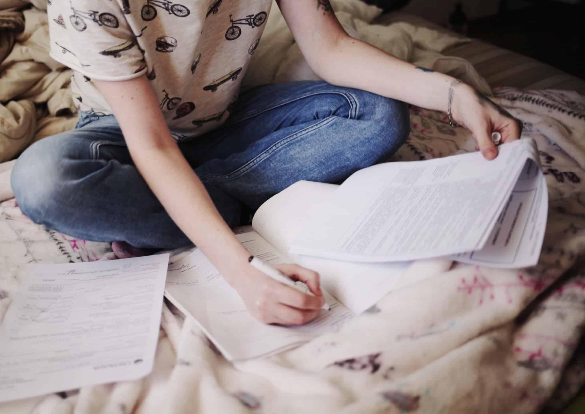 rapariga sentada na cama a escrever num papel