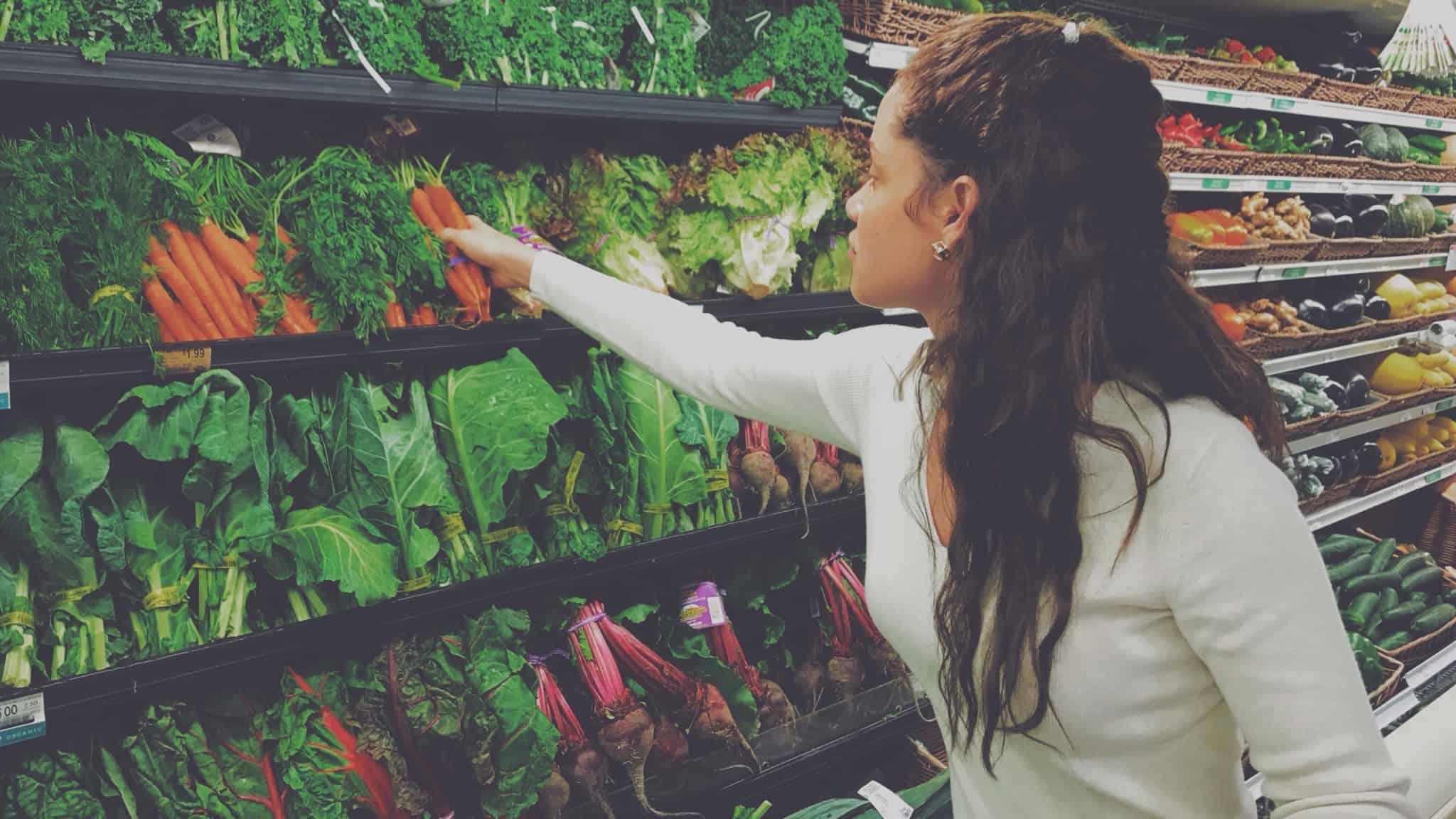 rapariga morena a escolher cenouras no supermercado