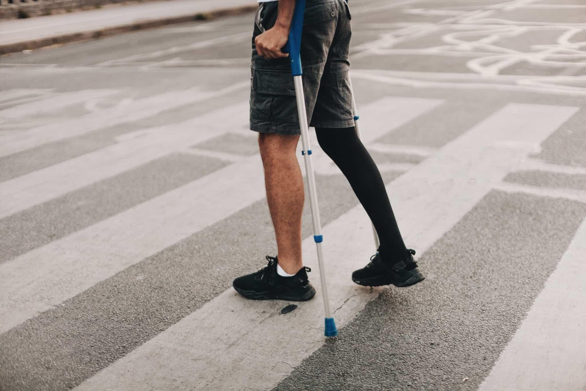 pessoa com muletas a passar uma passadeira