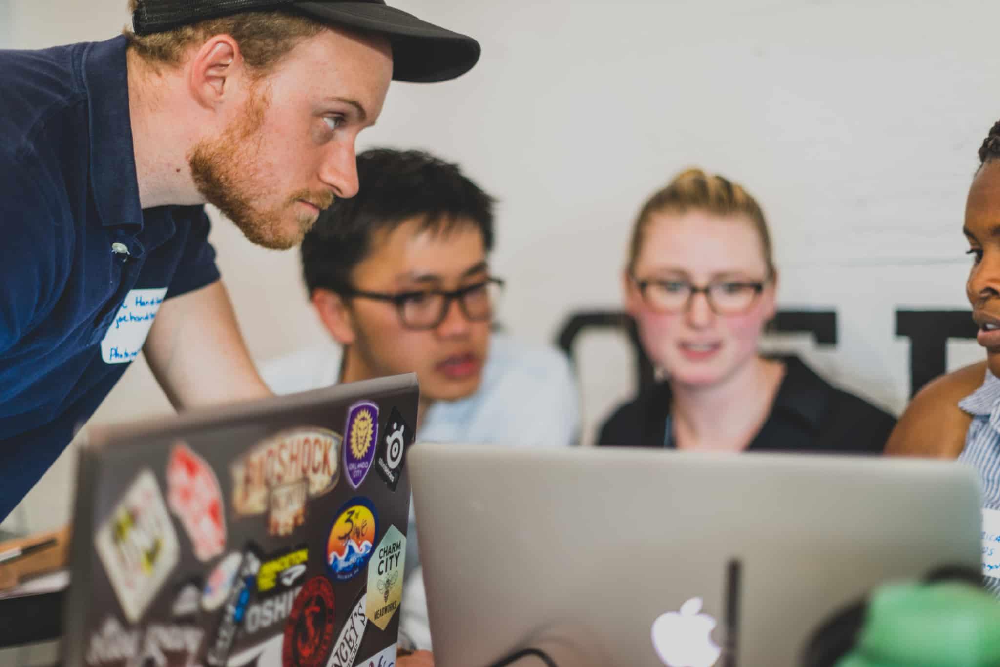 grupo de jovens, dois homens e uma mulher, trocam experiências em networking profissional