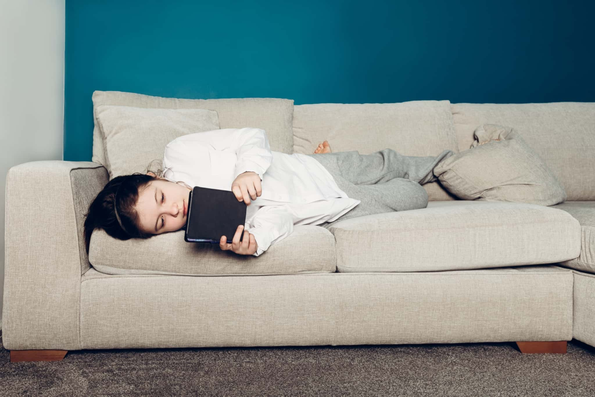 rapariga a ler um ebook deitada no sofá