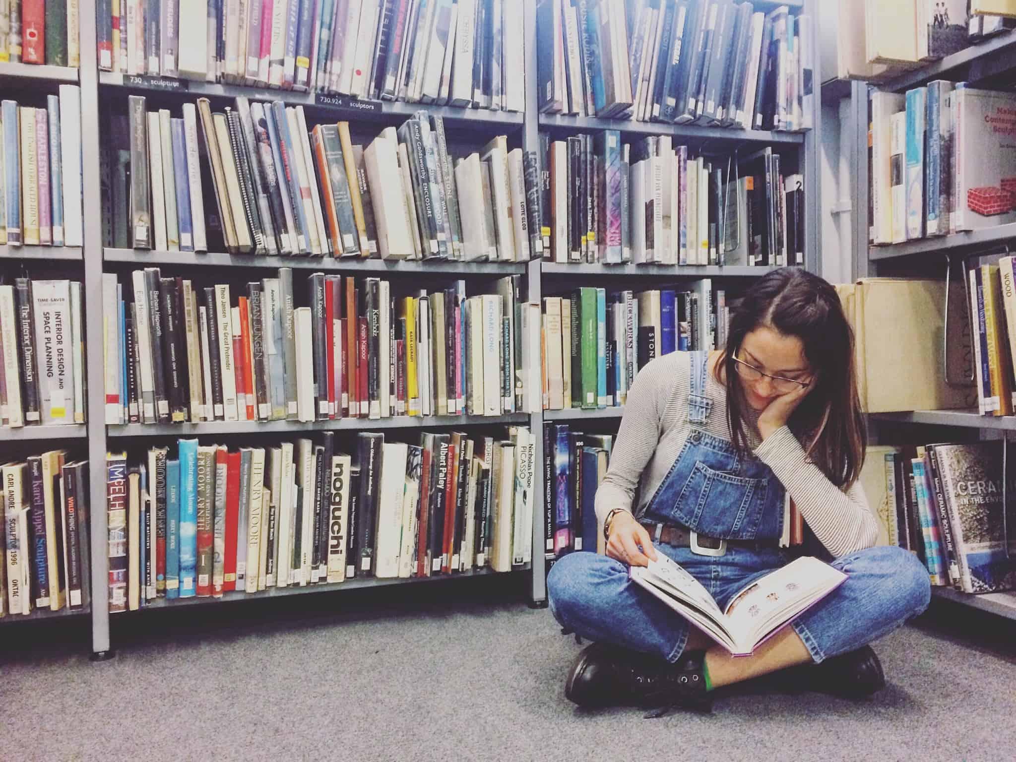 rapariga a ler no chão da biblioteca