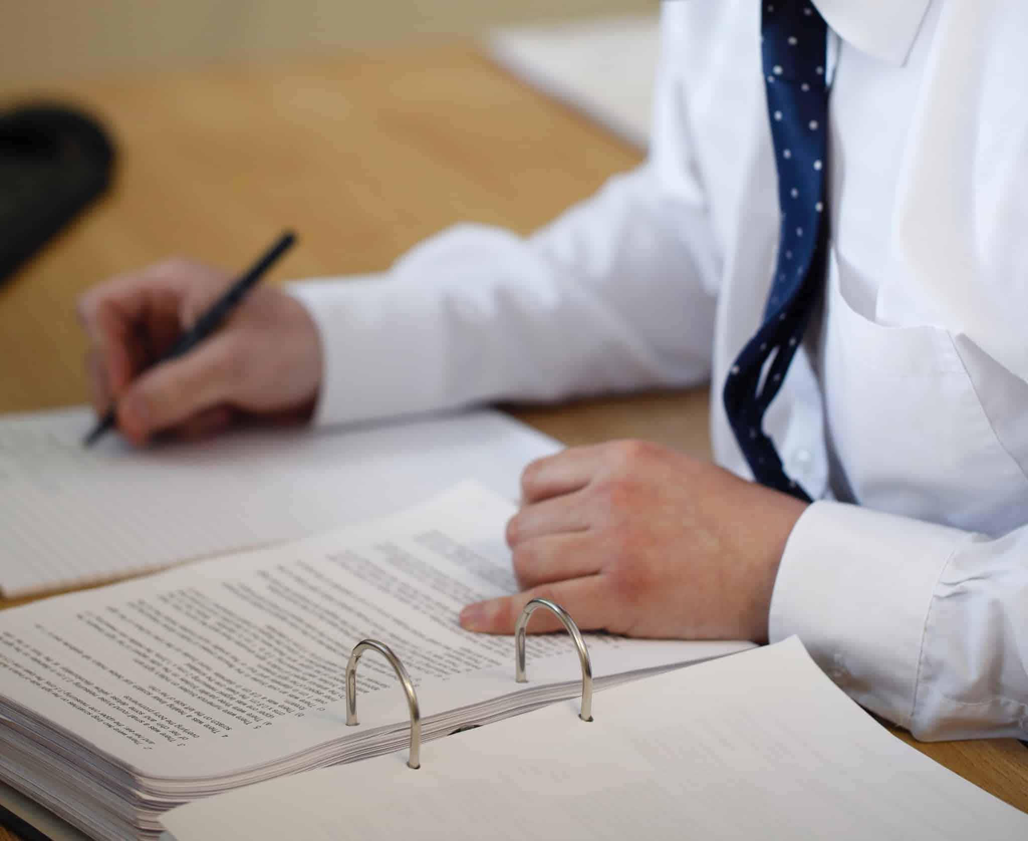 pessoa com gravata a escrever uma folha com um dossier aberto
