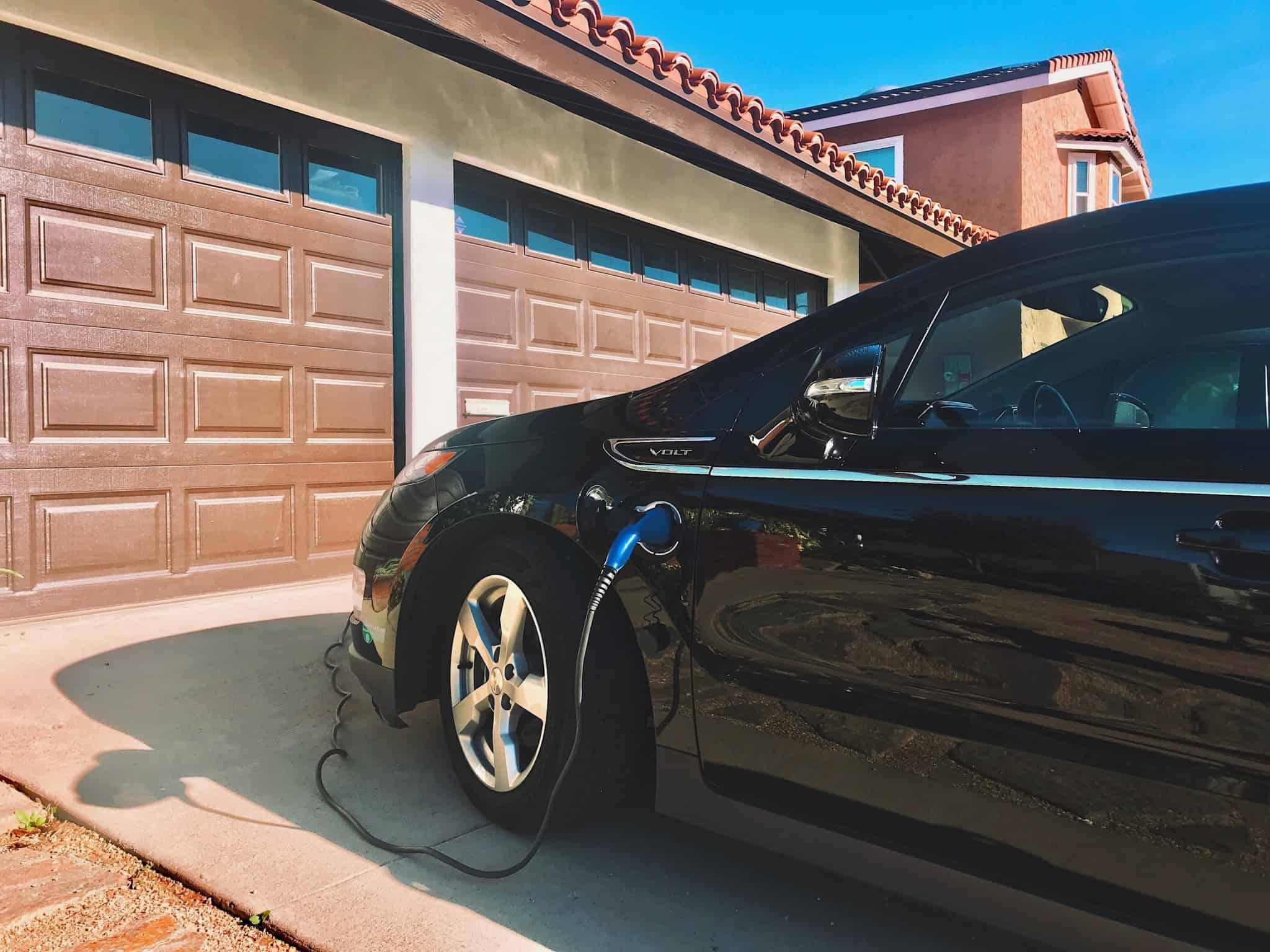 carro eléctrico a ser carregado à porta da garagem