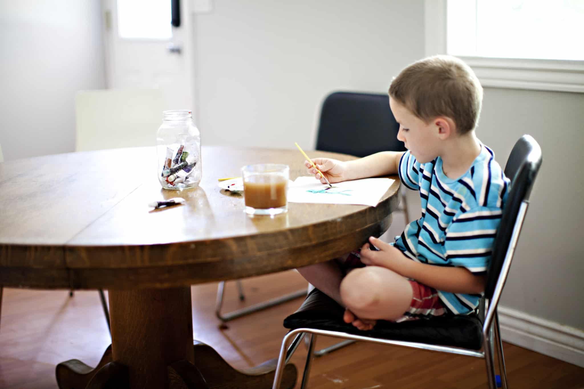 rapaz a pintar um desenho em cima de uma mesa