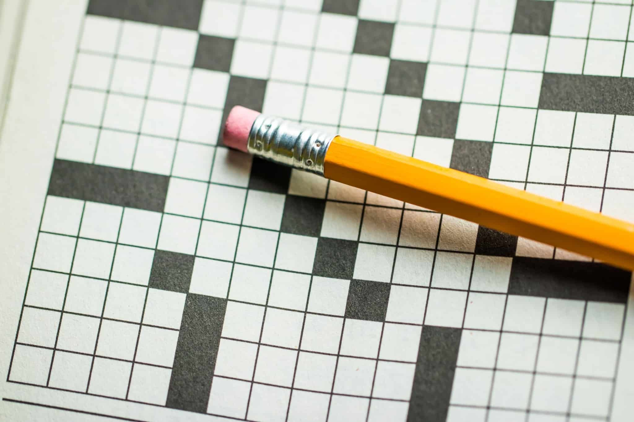 lápis em cima de um exercício de palavras cruzadas